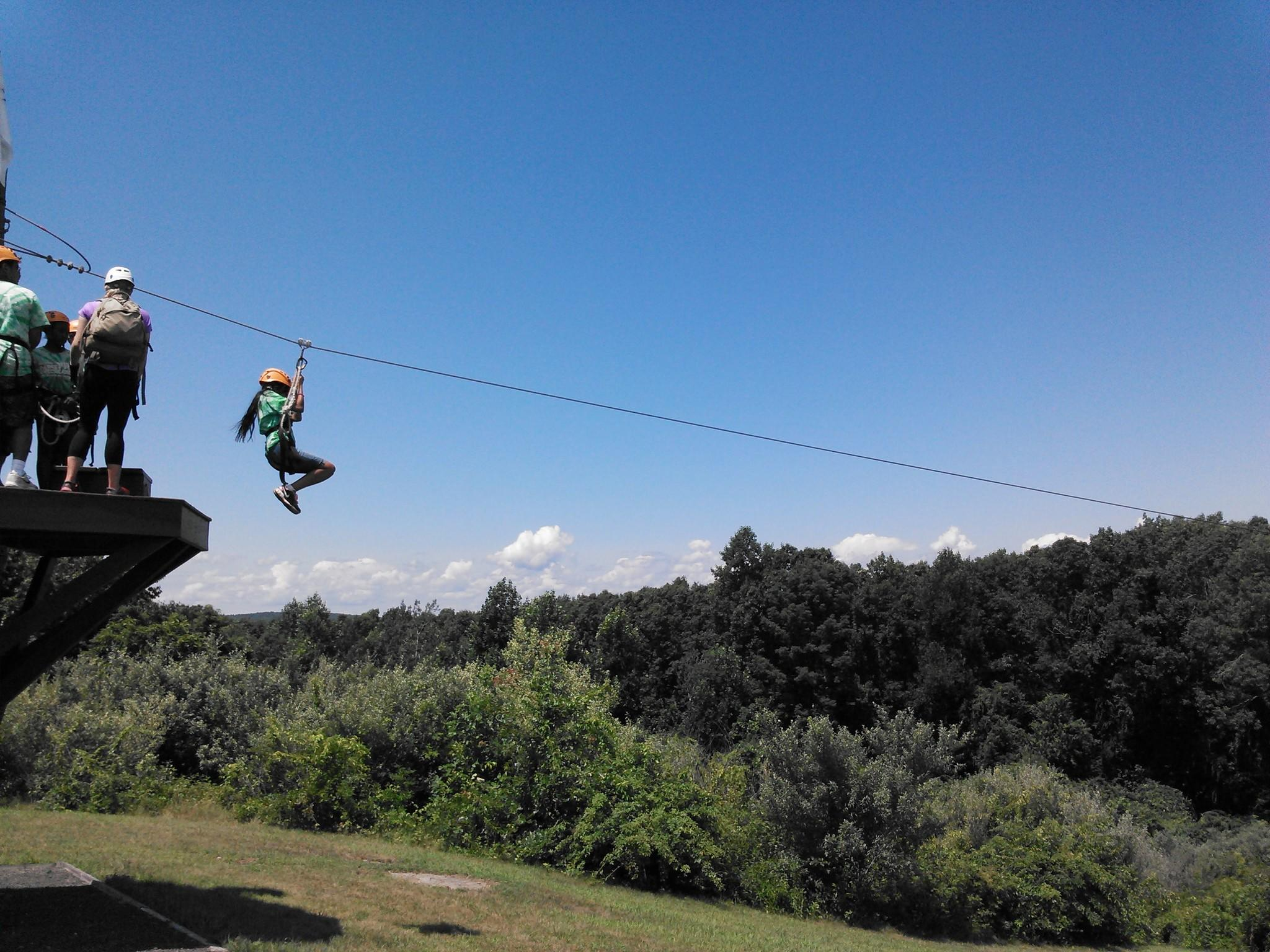 A young Leader in Training begins EMPOWER zip line canopy course.