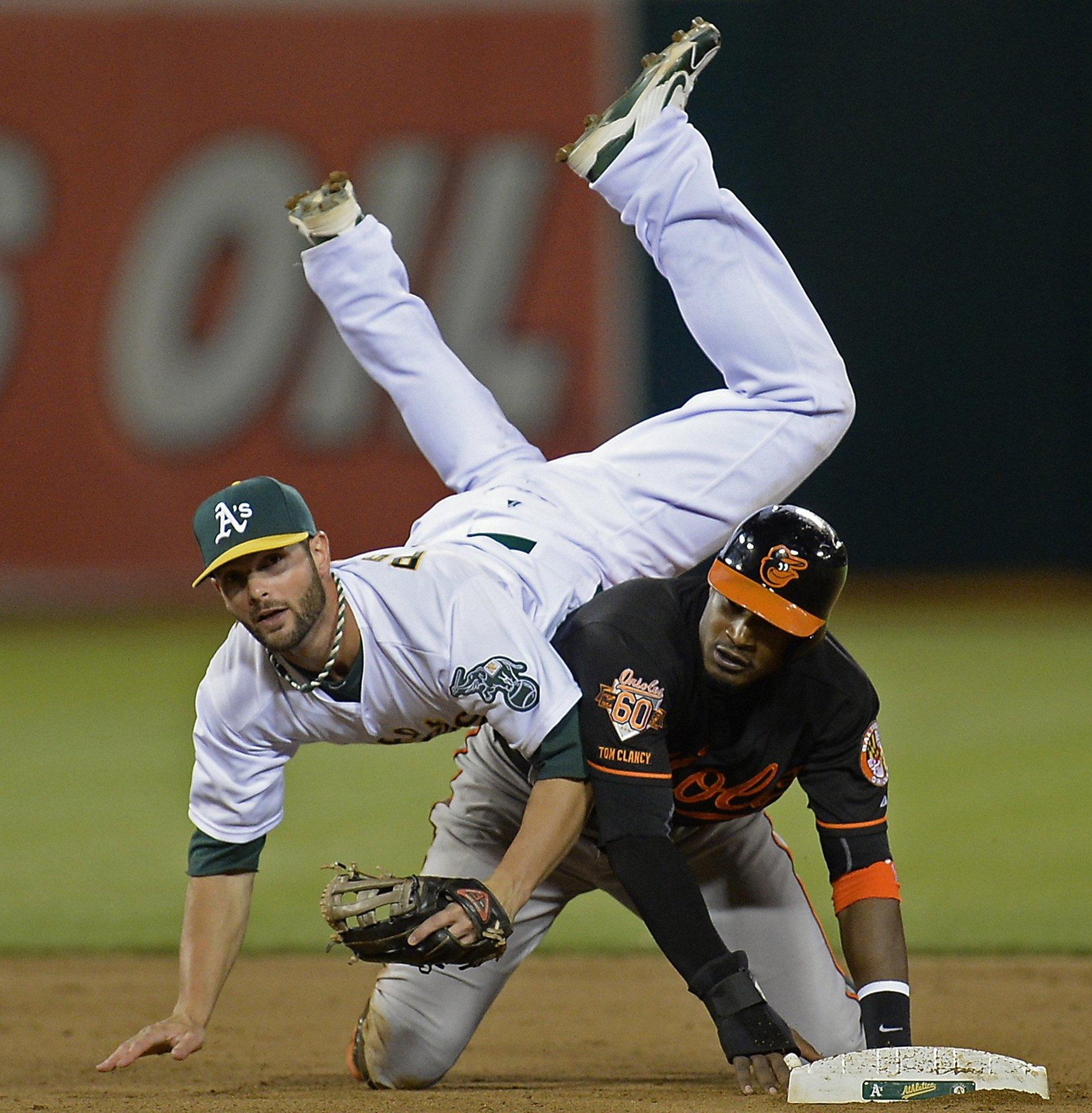 Oakland Athletics second baseman Andy Parrino lands on the Baltimore Orioles' Adam Jones after completing a double play in the eighth inning at O.co Coliseum.