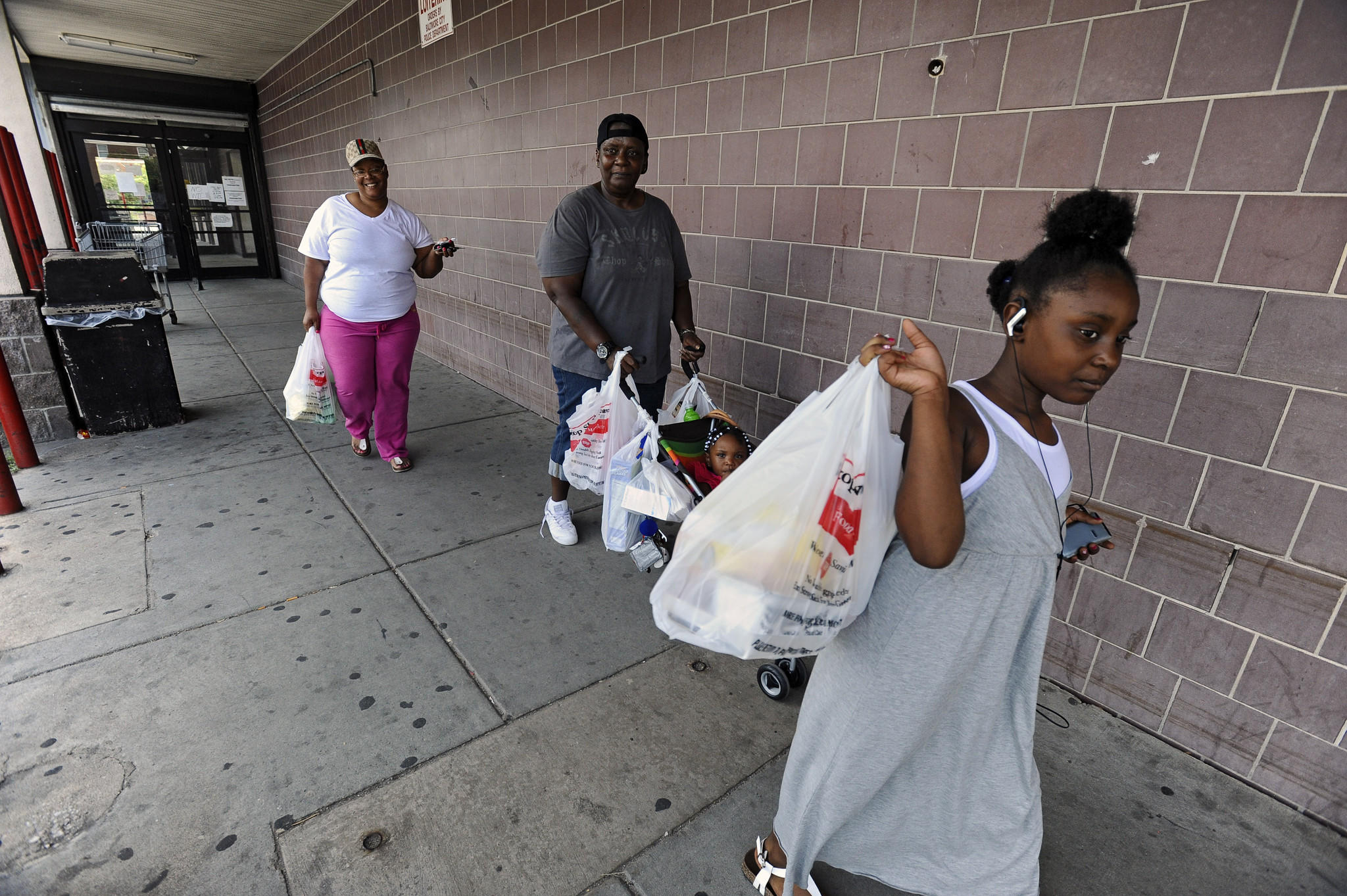 Tamia Allen, 8, right, leaves the Stop Shop & Save store at 1600 Harford Avenue in Baltimore with mother Lady Allen, from left, grand mother Marlene Ashe, who is pushing Kadidja Allen, 1.