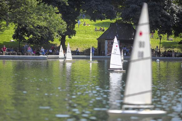 Park visitors in the distance operate remote control sailboats at the Conservatory Water in Central Park in New York.