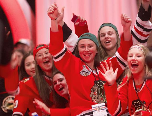 A group of young women cheer next to the red carpet at the opening ceremony of the Blackhawks Convention at the Hilton Chicago, July 18.