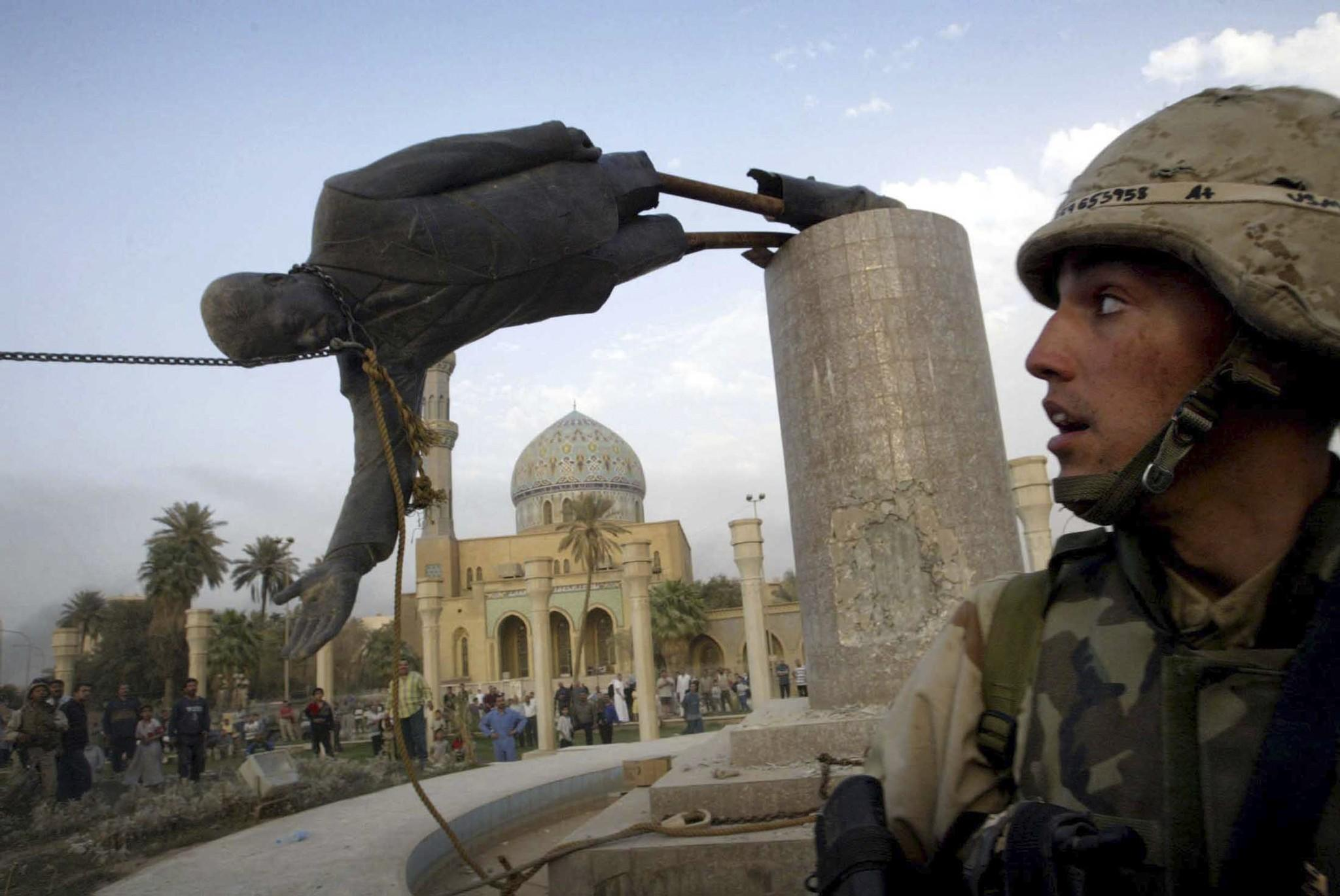U.S. Marine Corp Assaultman Kirk Dalrymple watches as a statue of Iraq's President Saddam Hussein falls in central Baghdad's Firdaus Square in this April 9, 2003 file photo.