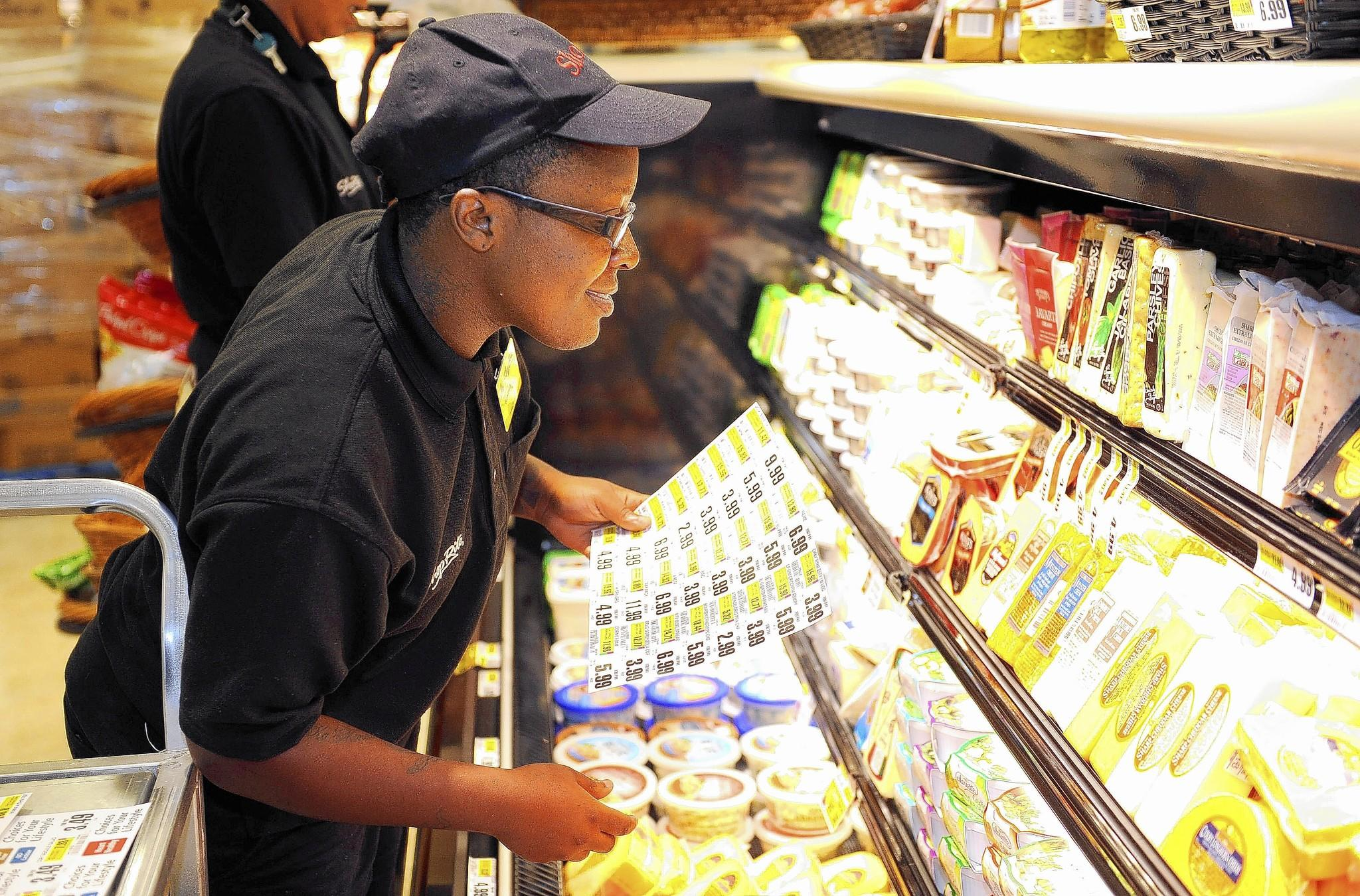 Keyona Young stocks one of the cases in the deli department at the new ShopRite store on Liberty Heights Avenue in Howard Park.