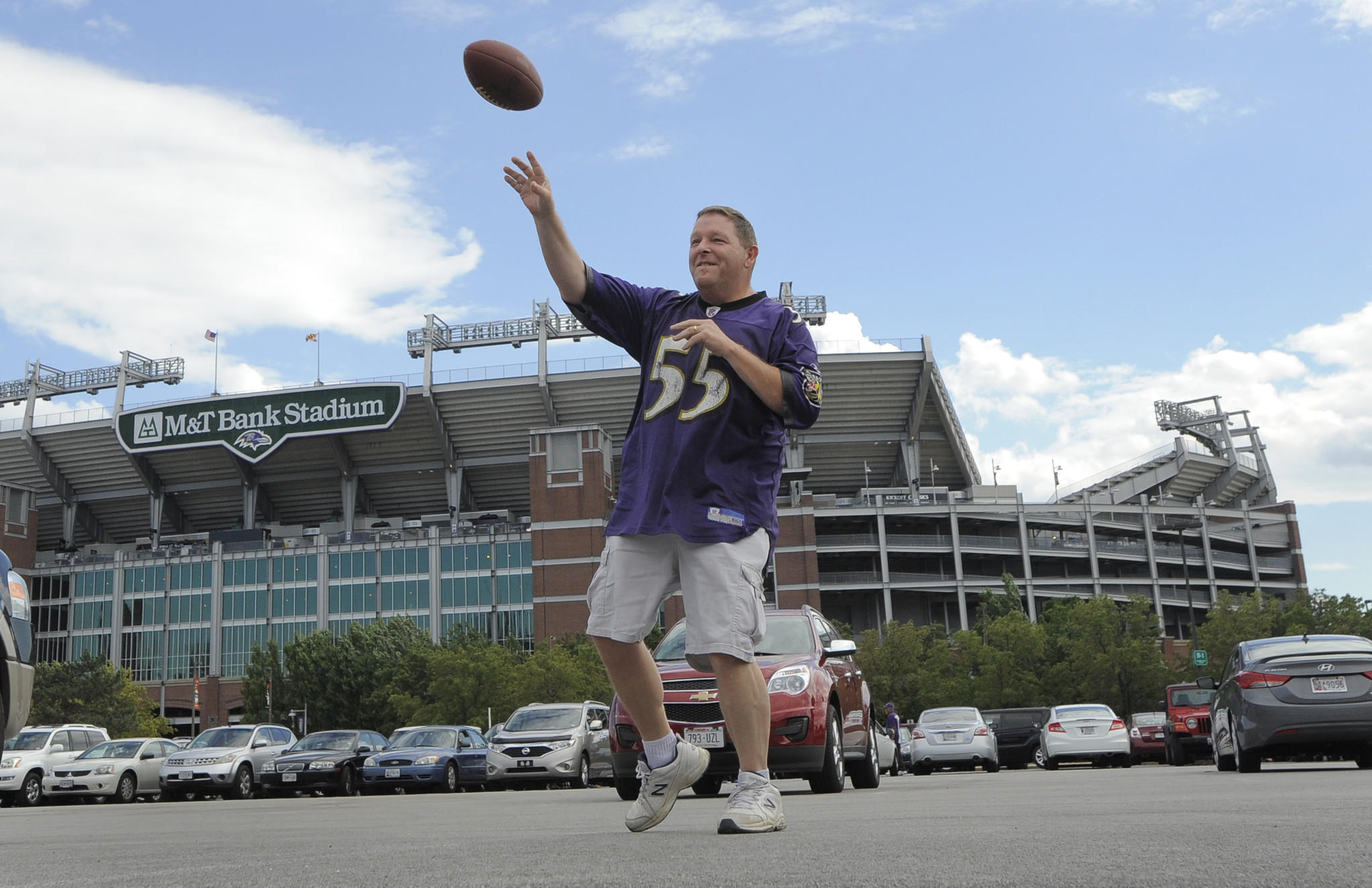 Chris Schreiner of Westminster throws a football during a tailgate outside the stadium before the Ravens practice. Baltimore Ravens hold their first public practice of the season at M&T Bank Stadium.