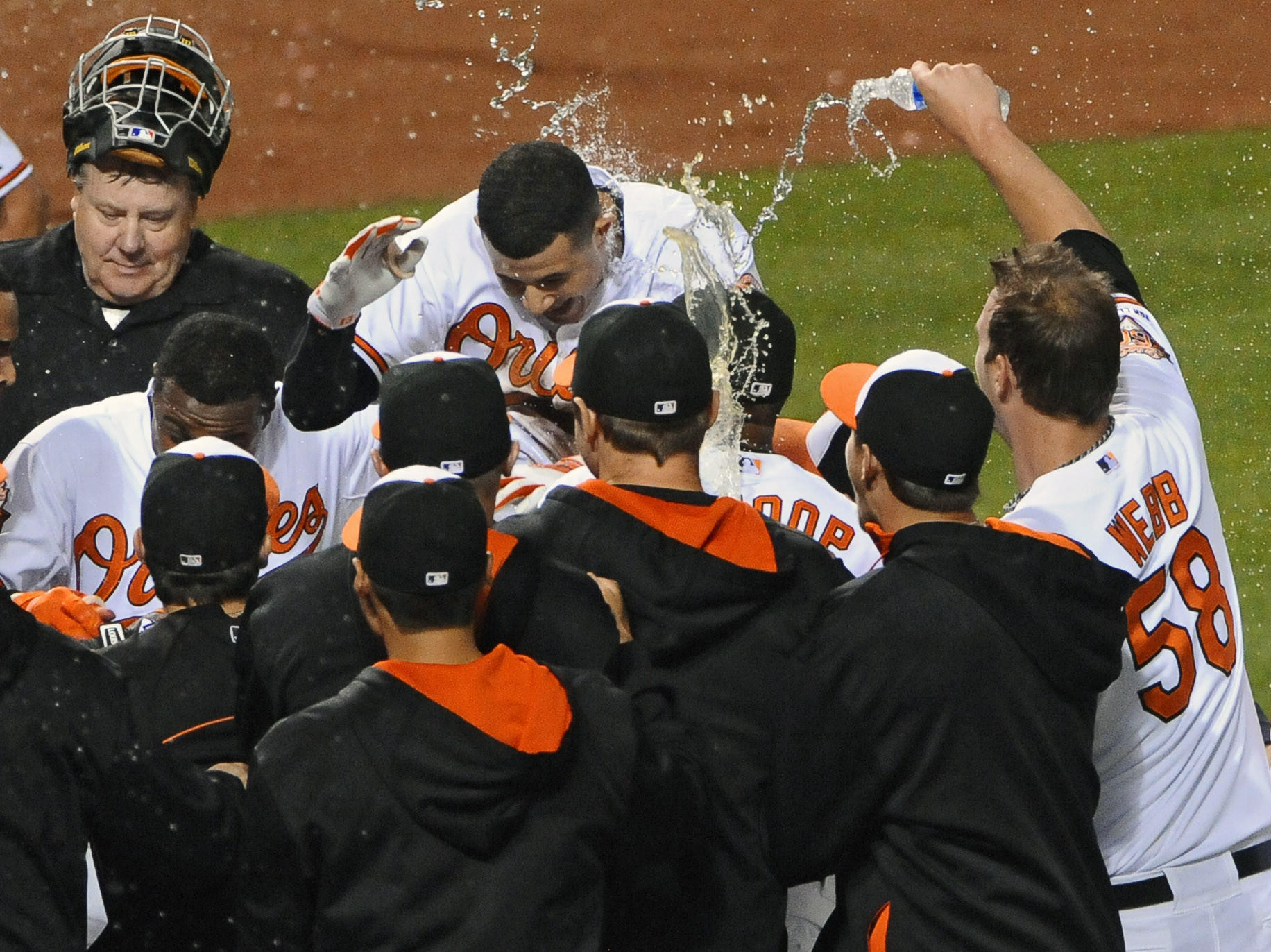 Third baseman Manny Machado, top, celebrates with teammates at home plate after hitting a walk-off home run to give the Orioles a 7-6 victory in 12 innings over the Los Angeles Angels at Camden Yards.