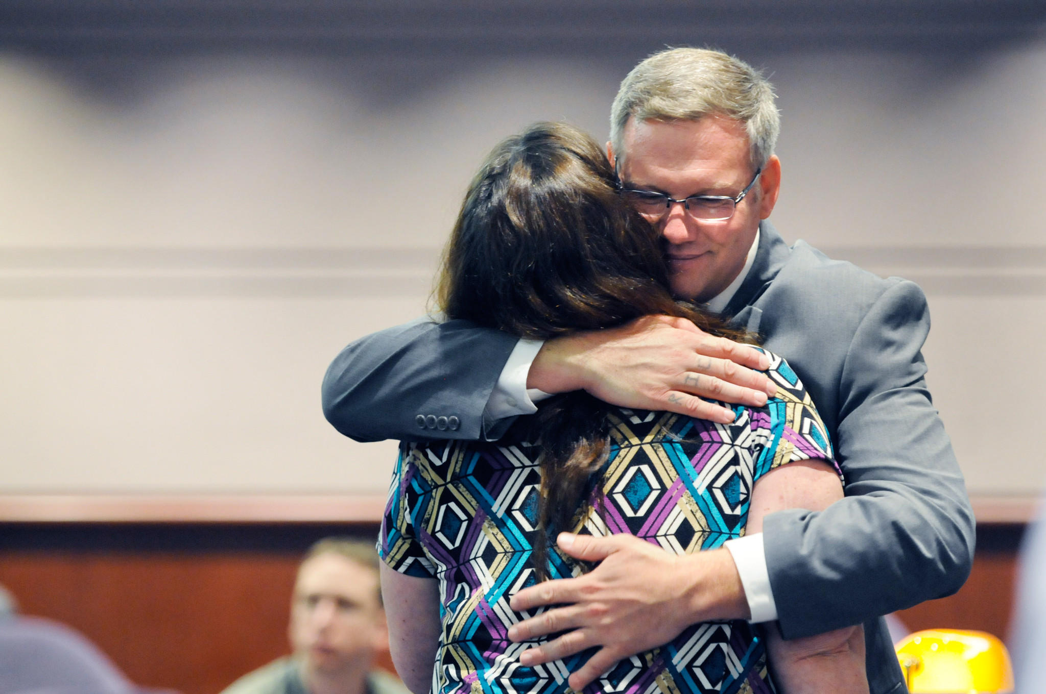 Kenneth Ireland hugs his sister, Lauri Hinojosa, during a break in a hearing before the Office of the Claims Commissioner. Ireland is seeking up to $8 million in compensation from the state after serving 21 years of a 50-year sentence for a rape and murder he did not commit.