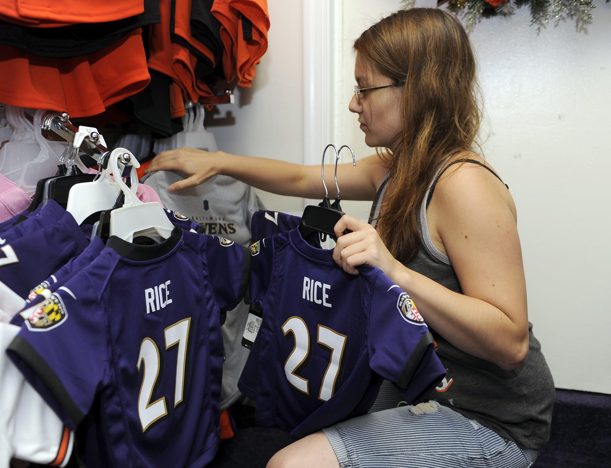 Lindy Burruss, a sales associate at Wild Bill's sporting goods on Belair Road, straightens a display of toddler-sized Ray Rice and other jerseys.
