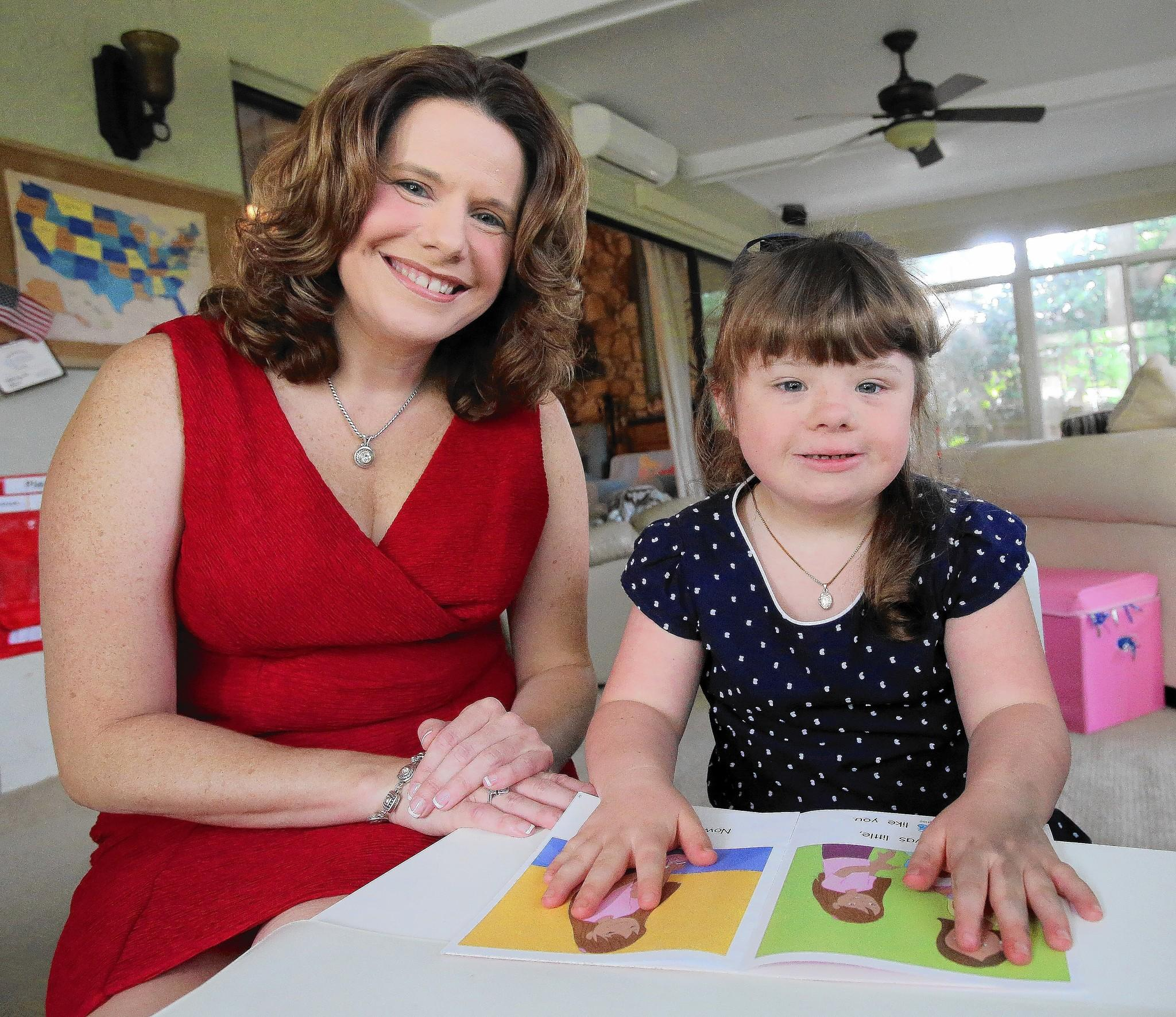 Julie Kleffel with her daughter, Faith, 7, in their Longwood home. Faith has Down Syndrome, and Kleffel hopes that the new state-supported scholarship will help cover the cost of tutors and therapists Faith needs.