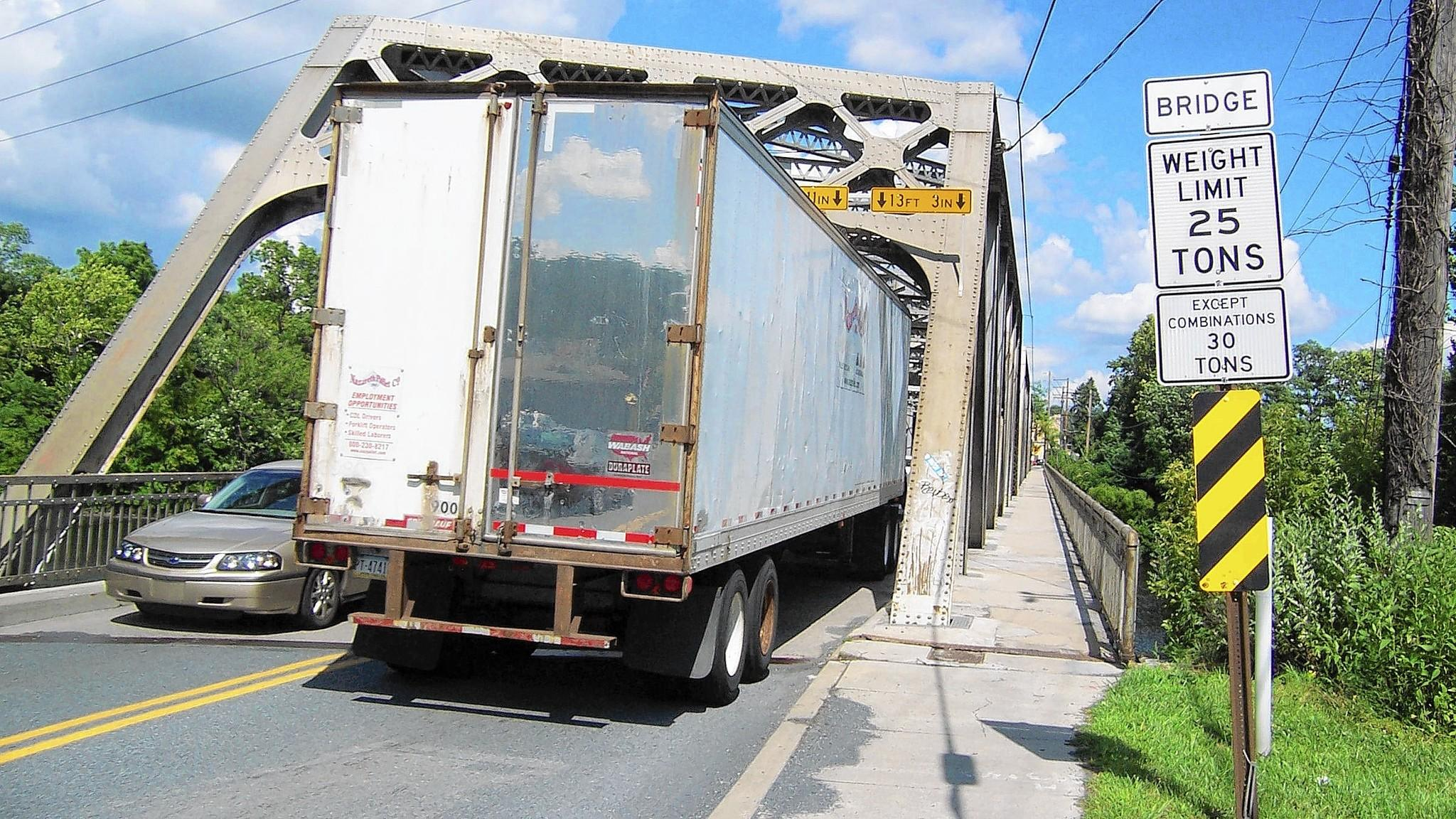 It's a tight fit, but tractor-trailers can, and do, squeeze across the weight-restricted Cementon-Northampton Bridge. The real concern is the weight of large trucks crossing the structurally deficient span.