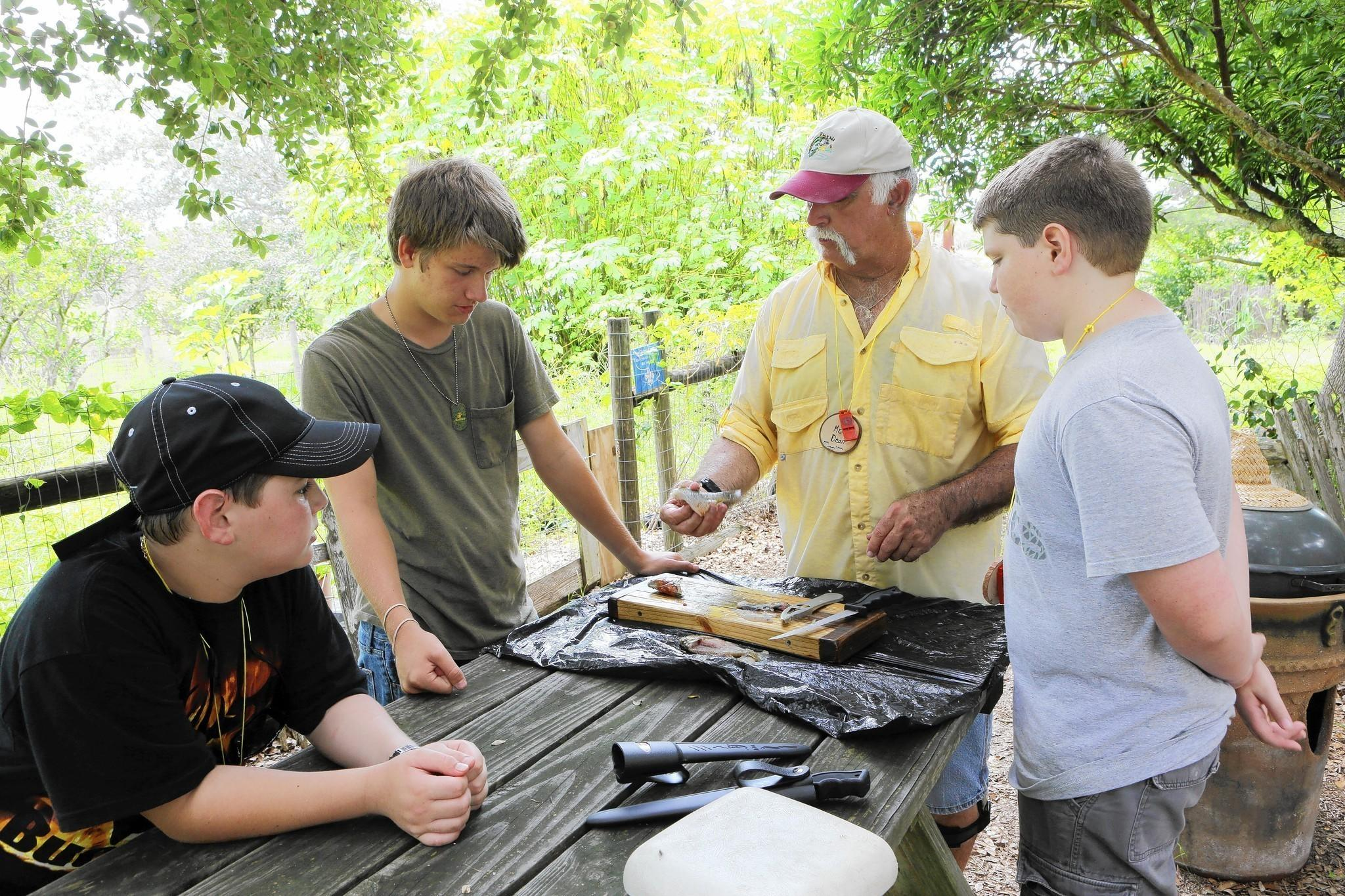 Dean Morris teaches Dylan Abbott, 11, left, Christian Paup, 15, and Jeremy Porter, 12, how to filet fish.