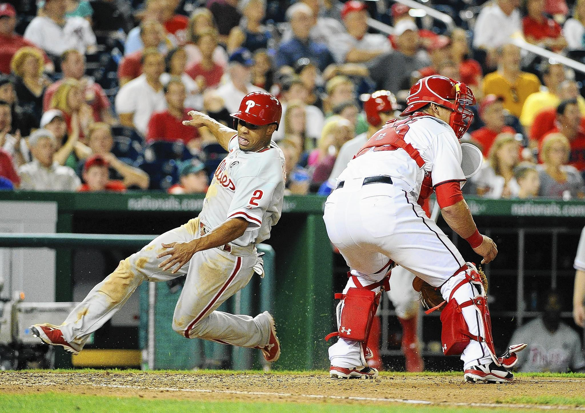The Phillies' Ben Revere slides safely home as Washington catcher Wilson Ramos waits for the throw.