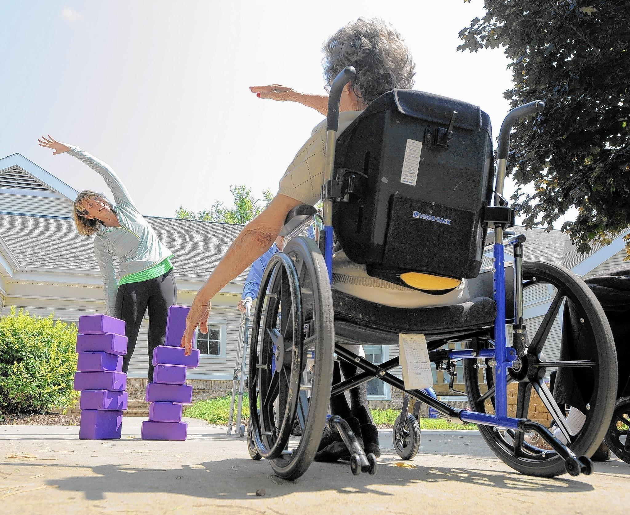 Cathy Rees teaches a yoga class for people with dementia at Copper Ridge, an assisted living center. Darlene King (right), a resident at the center, follows along.