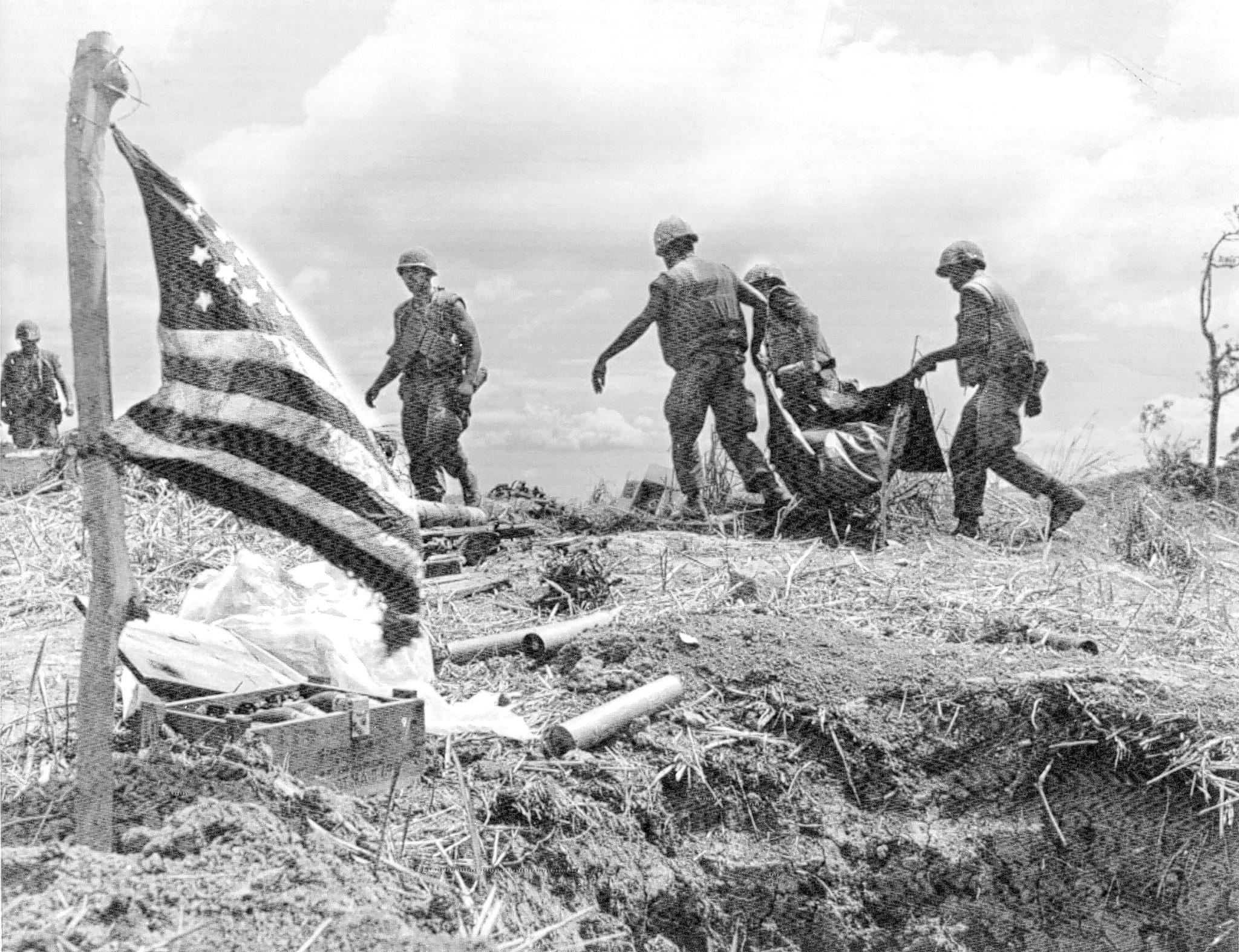 Marines gather bodies of dead comrades atop a battlefield hilltop just south of Khe Sanh in June 1968. Vietnam one photo.