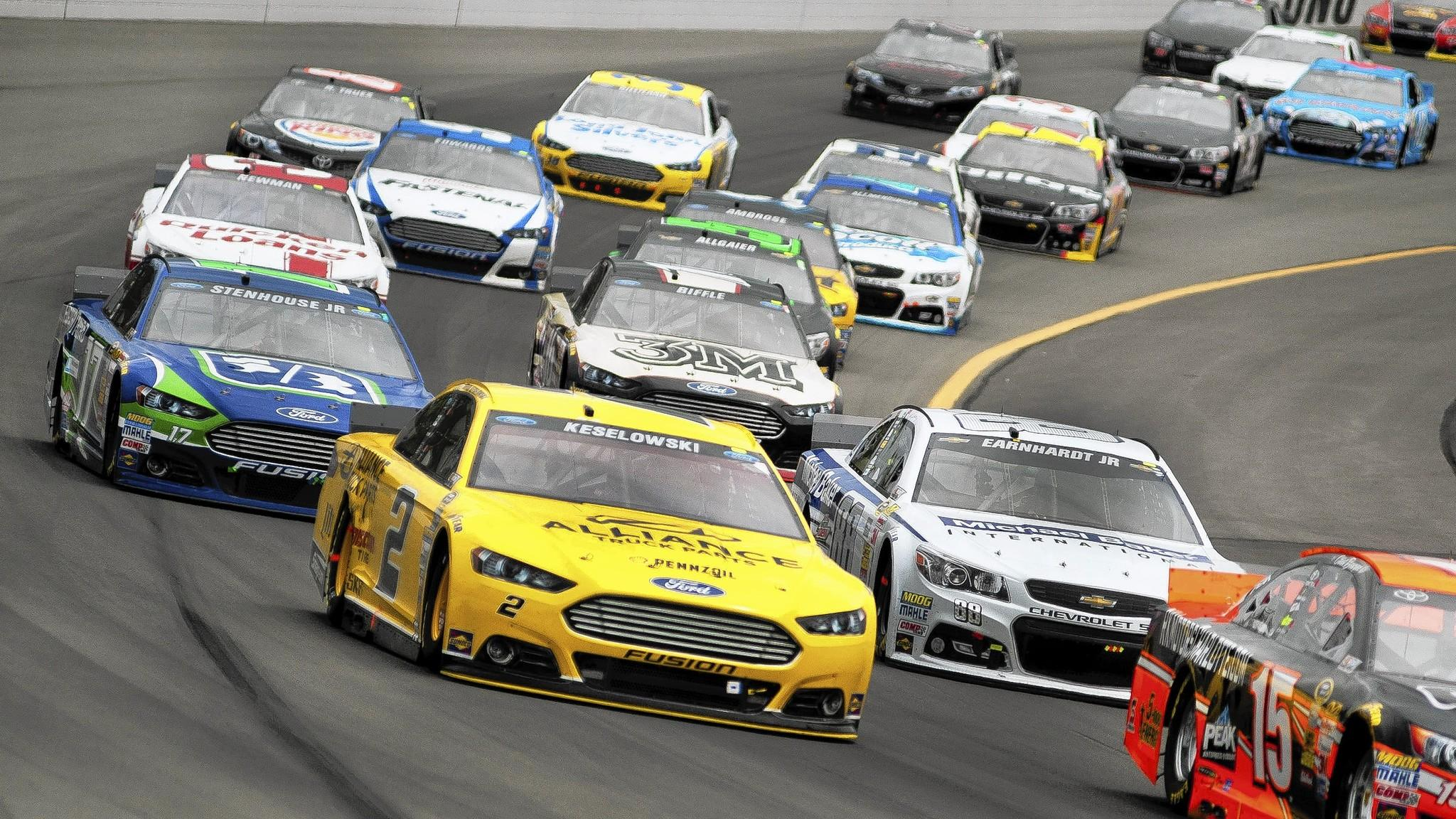 A crowded field of cars moves into Turn 2 after a restart on Sunday at Pocono International Raceway in Long Pond during the GoBowling.com 400.