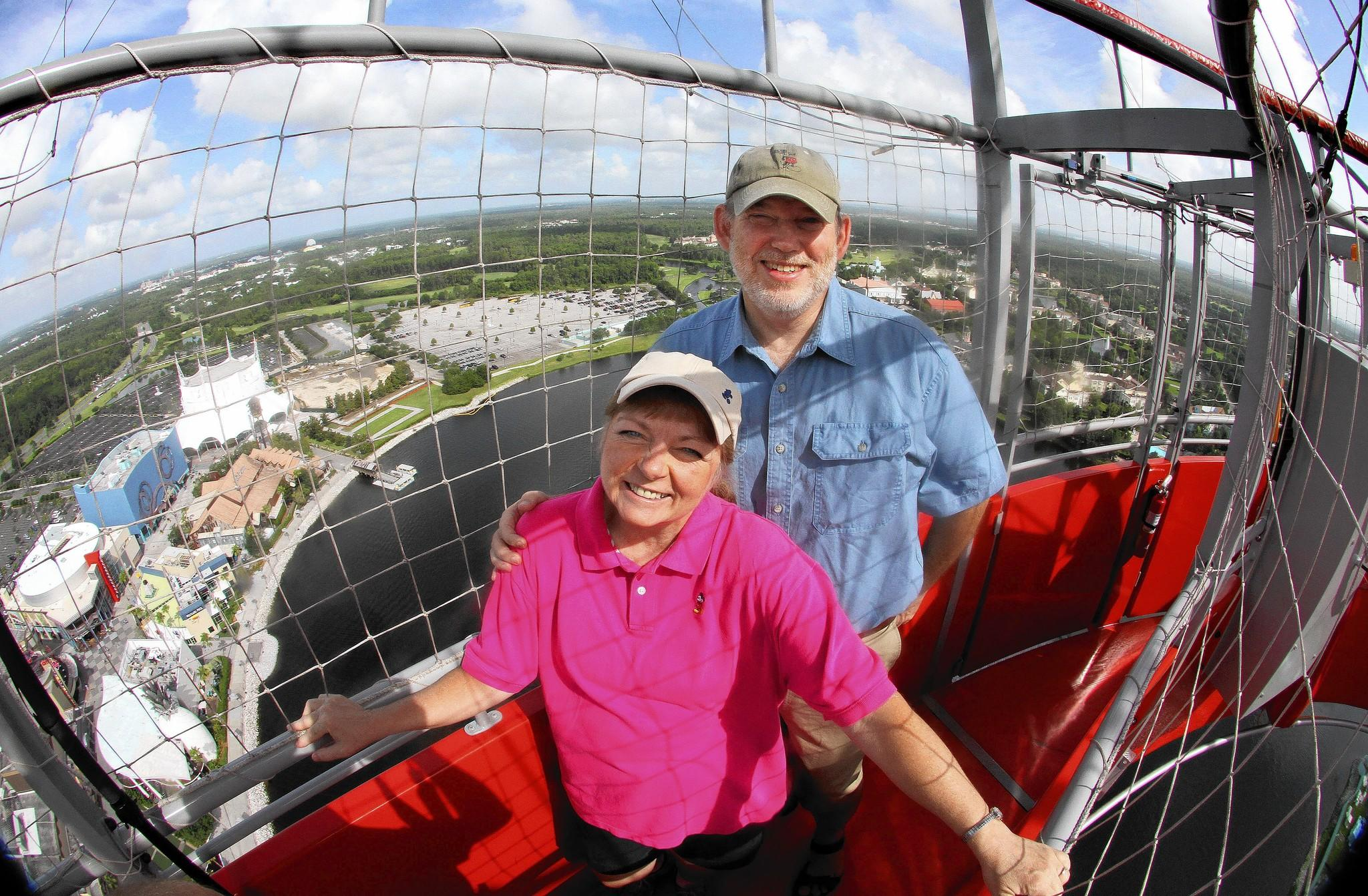 Julie and Mike Neal, producers of a popular Disney World travel guide, ride the Characters in Flight helium balloon over Downtown Disney.