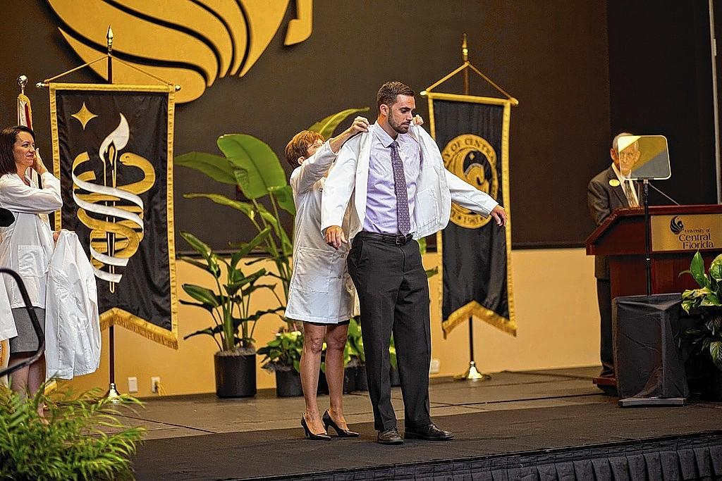 Former UCF soccer player Kyle Cox receives his white coat after his admission to the College of Medicine.