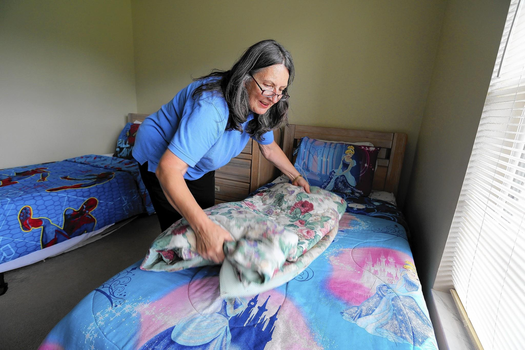 FloridaDreamHomes.com co-owner Karin Boyer folds linens in a bedroom in one of the rental properties they manage, so the Kissimmee house is ready for renters who will arrive later in the day.