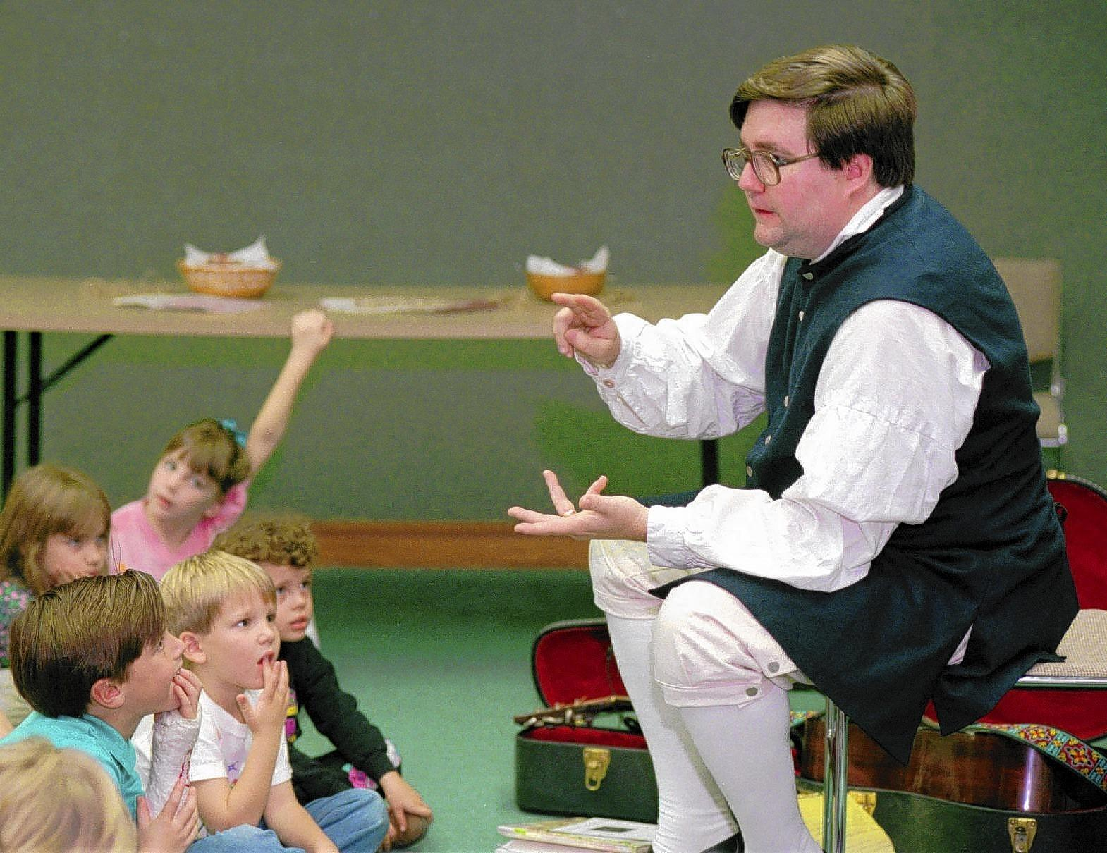 """Storyteller and historian Oscar """"Skip"""" Booth is shown in the 1993 photo sharing a story about Colonial Thanksgiving with kids at North County Library."""