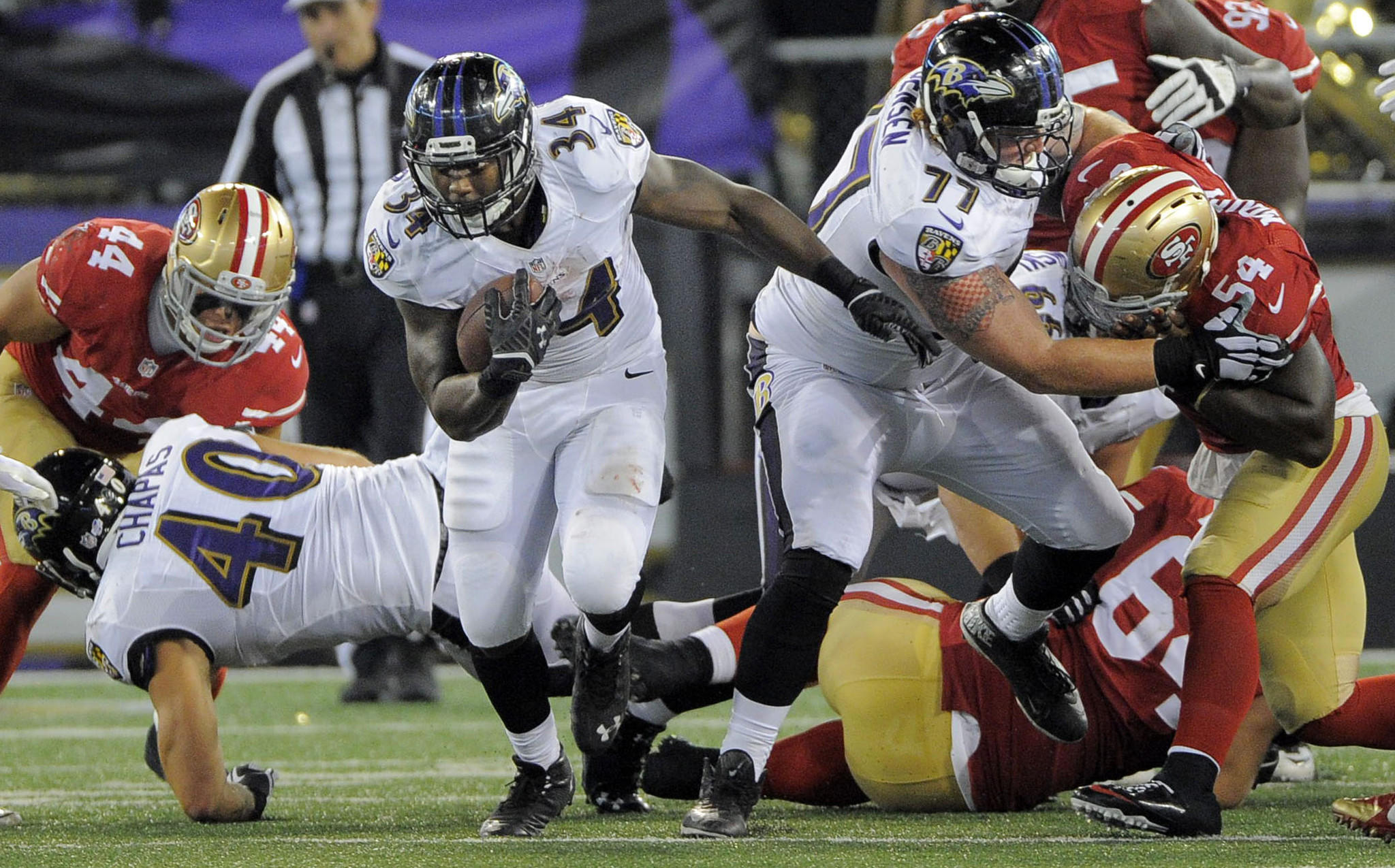 Ravens running back Lorenzo Taliaferro finds a hole against the 49ers as Ravens offensive linemen Shaun Chapas and Ryan Jensen provide blocks.