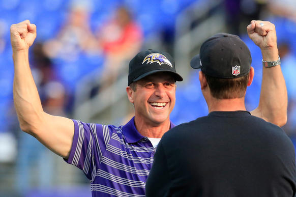 Ravens coach John Harbaugh chats with his brother 49ers head coach Jim Harbaugh before the teams played their preseason opener on Thursday.