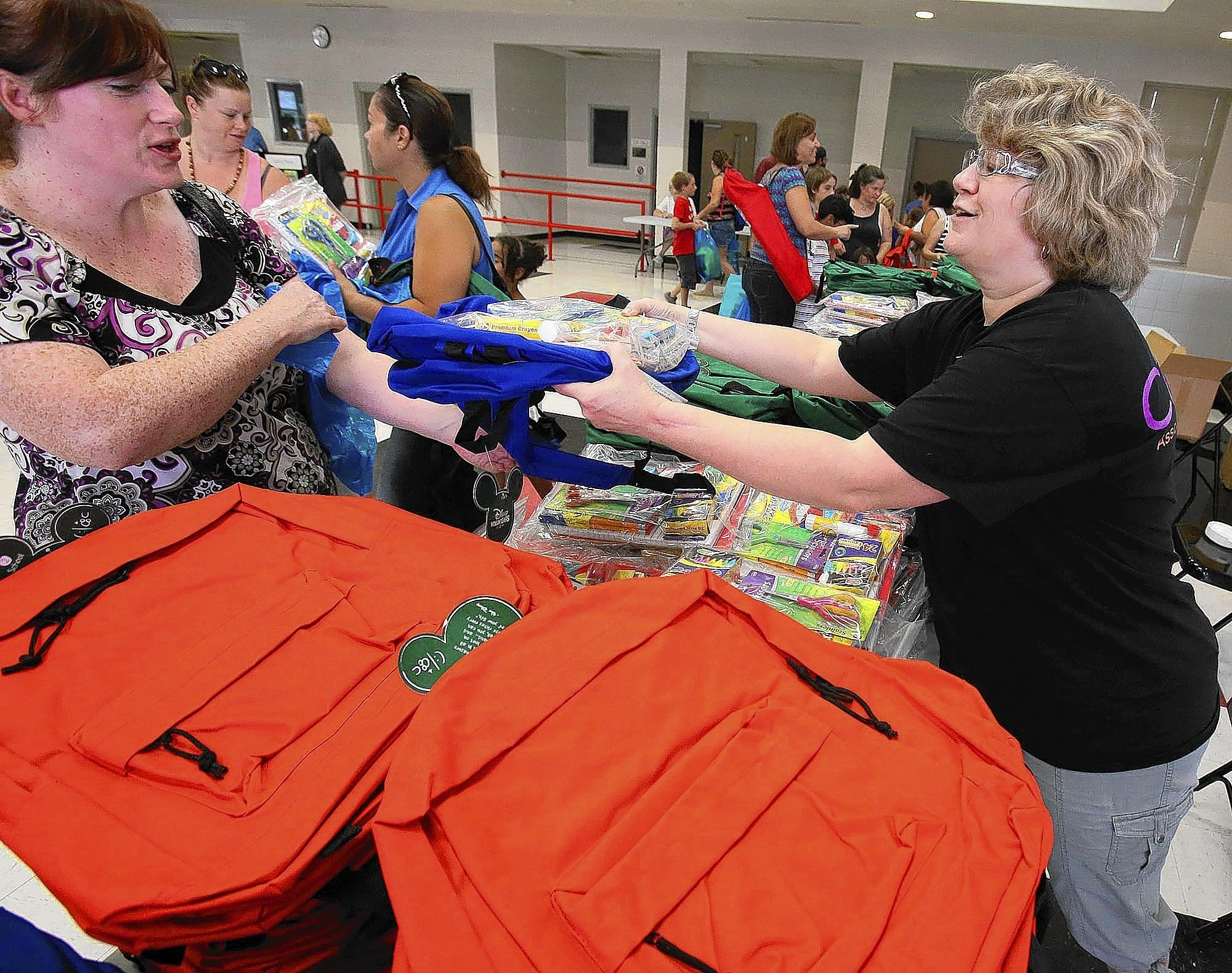 Terrie Lombard, right, hands out backpacks during a Back to School ...