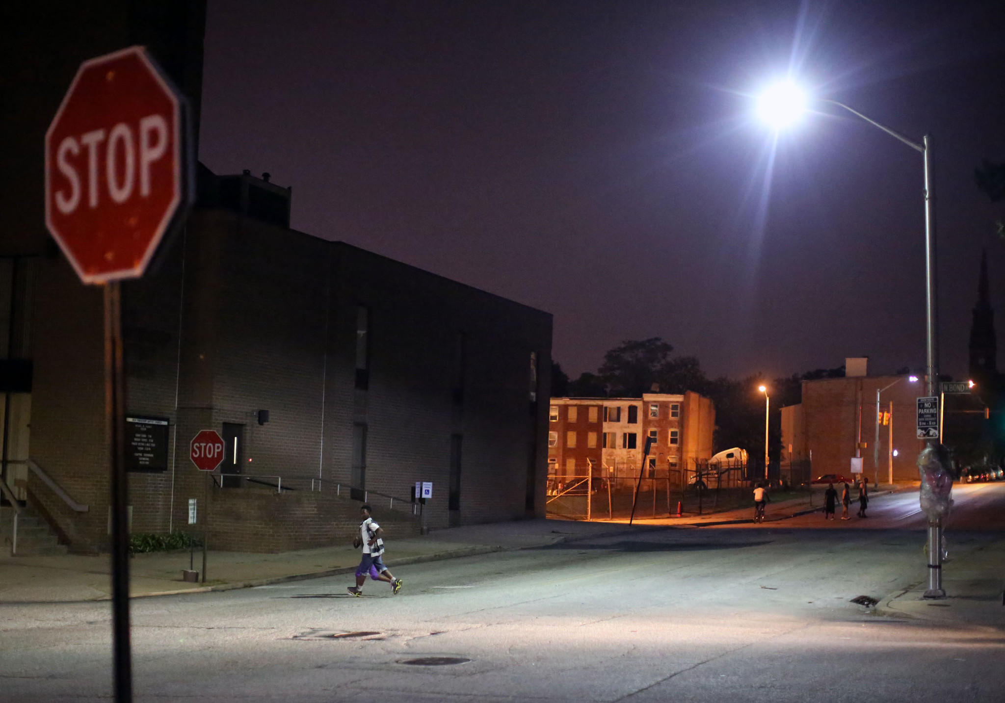 An 11-year-old boy crosses the street in East Baltimore just two minutes before the 9 p..m Baltimore City curfew for youth.