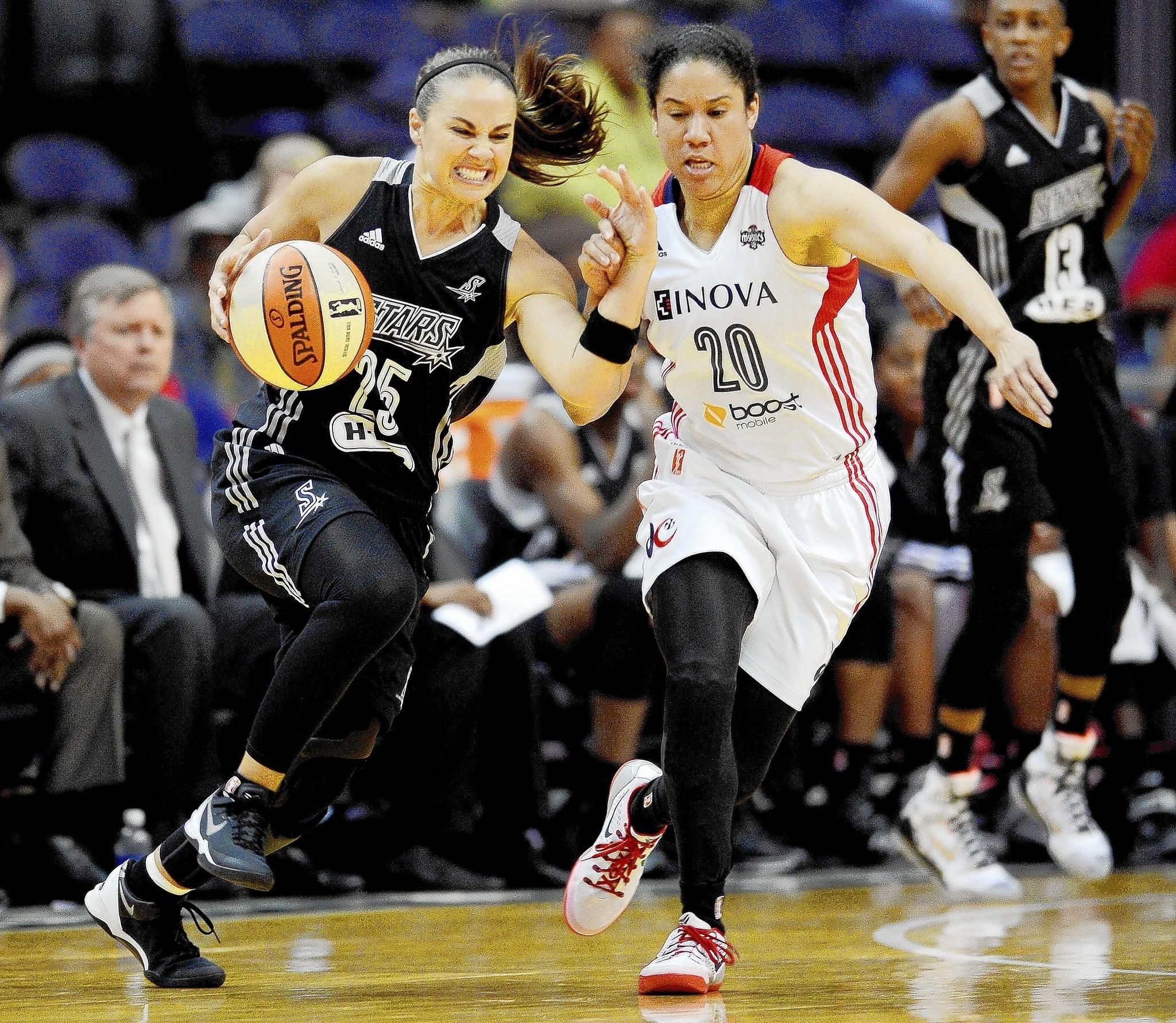 San Antonio Stars guard Becky Hammon (25) tangles with Washington Mystics guard Kara Lawson (20) as she dribbles in the fourth quarter at the Verizon Center in Washington, Sunday, June 29, 2014.