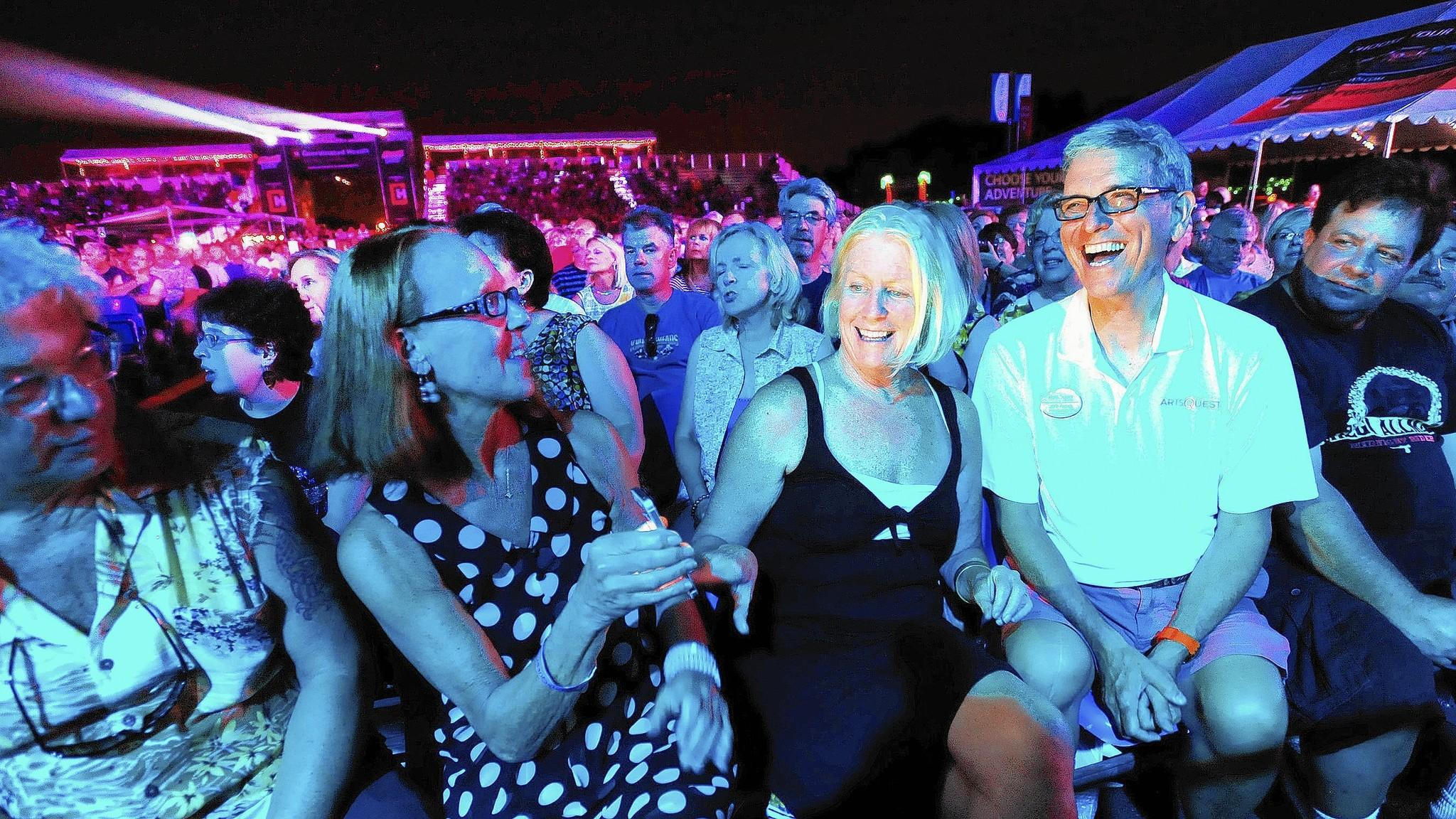 Outgoing ArtsQuest chief Jeff Parks sits in the front row and watches the Moody Blues under dim stage lighting Tuesday, August 5, 2014. He is sitting with friends from left: Marty and Robin Staff of Springtown; Kathy Calabrese of Bethlehem. ///// BETHLEHEM DONNA FISHER/THE MORNING CALL Pic made TUESDAY, AUGUST 5, 2014