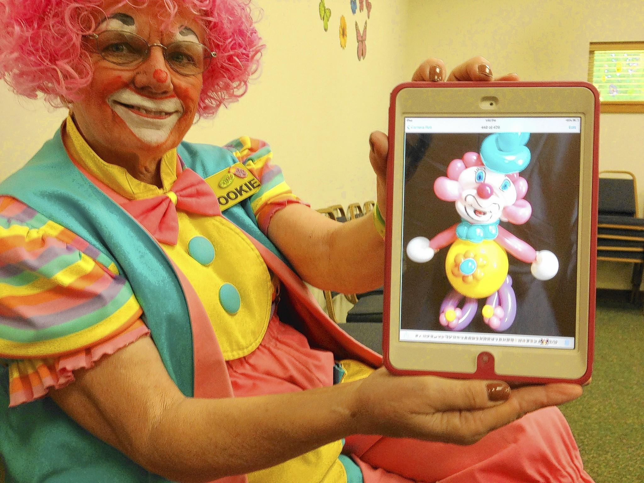 "Carol Meyer of Casselberry, whose clown name is ""Cookie,"" shows a photo of a ""self-portrait"" baloon sculpture during an appearance at the W.T. Bland Public Library in Mount Dora."