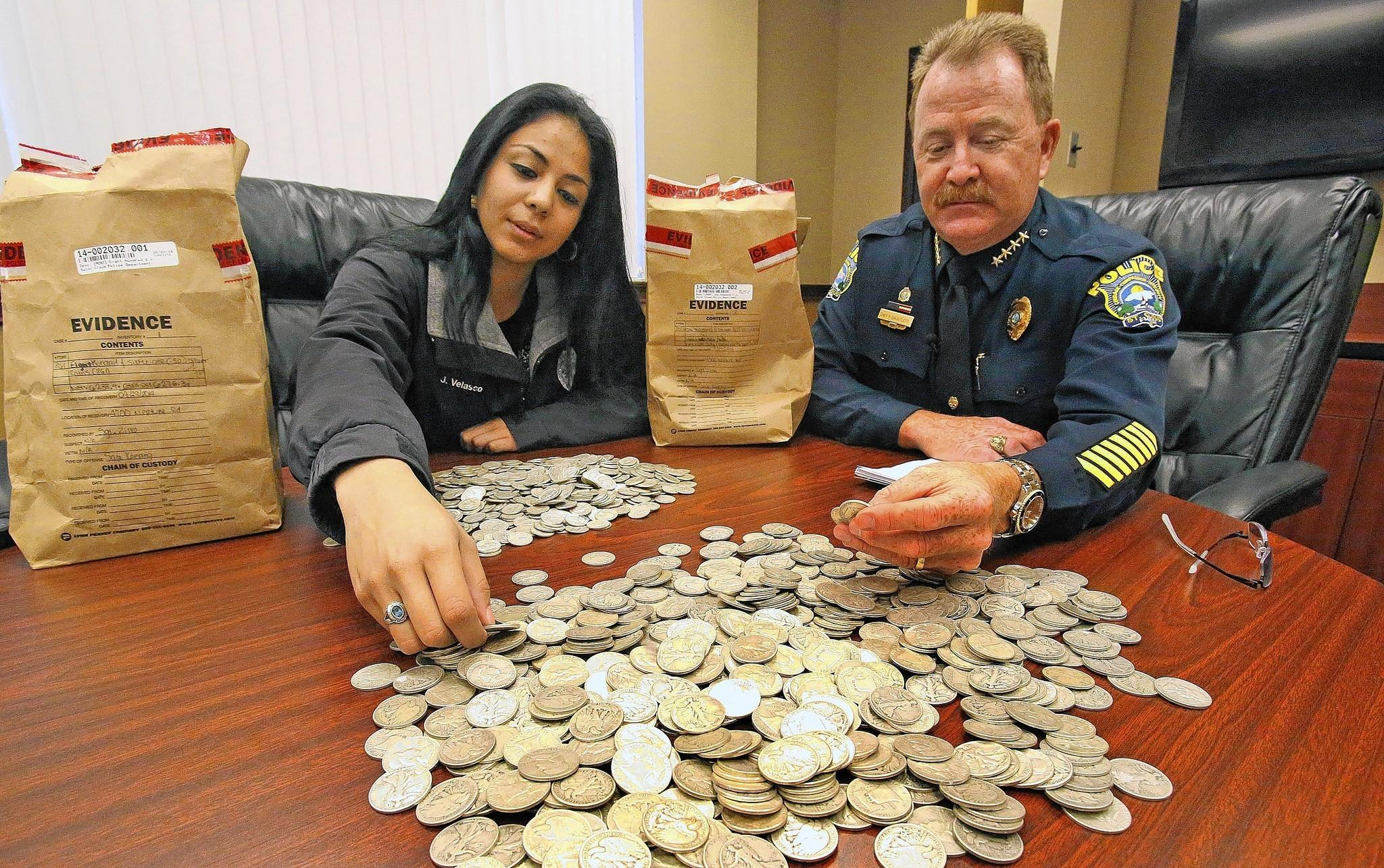 St. Cloud police crime-scene technician Jessica Velasco and Chief Pete Gauntlett sort some of the thousands of silver coins found in a condemned house.