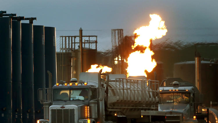Tanker trucks for hauling water and fracking fluids line up near a natural gas flare in Williston, N.D. Fracking has touched off a nationwide oil and gas boom, and with it, worries about public health and the environment. (Charles Rex Arbogast / AP)