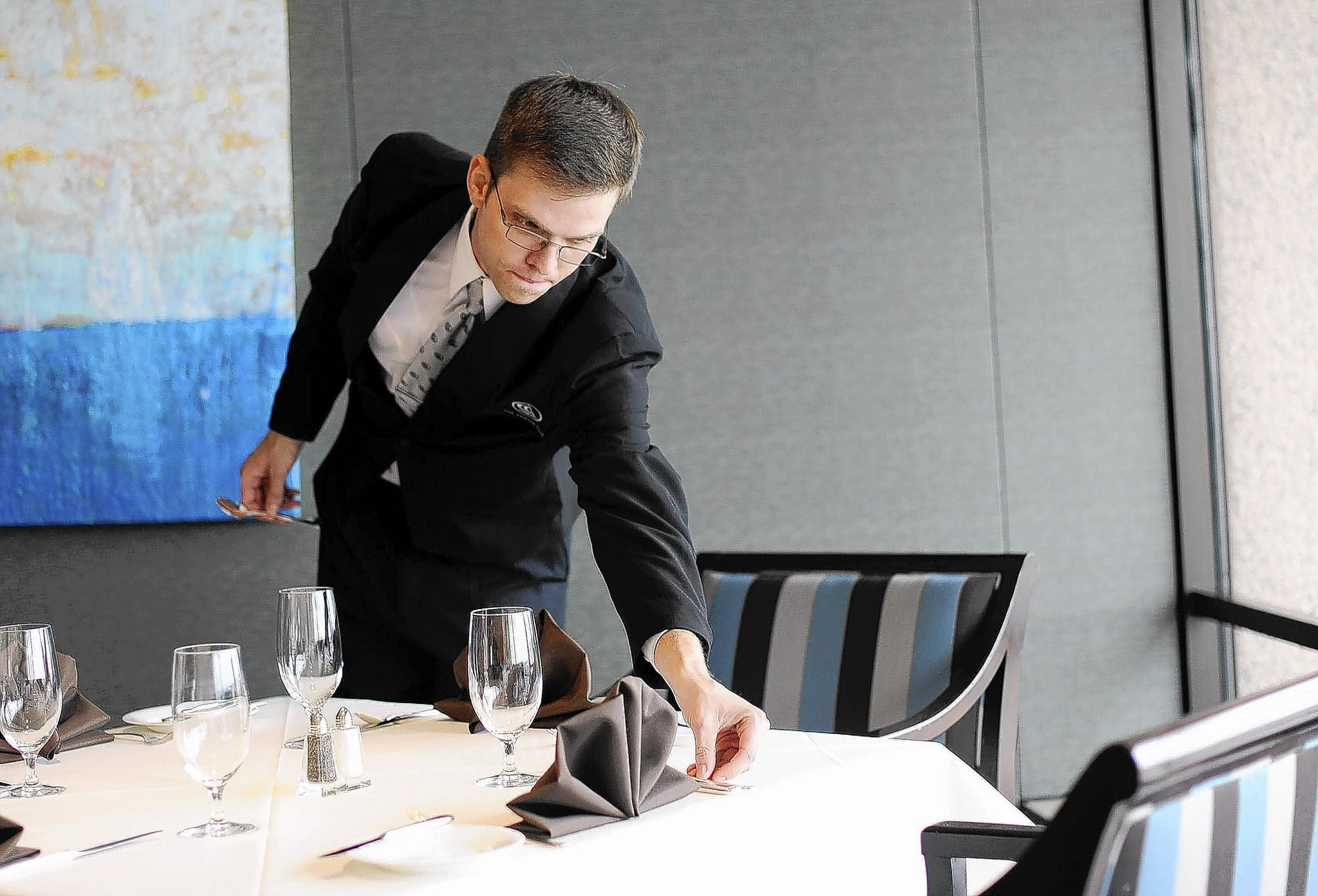 Server Matthew Lowe, of Baltimore, sets up tables with silverware and napkins for lunch in the Center Club.
