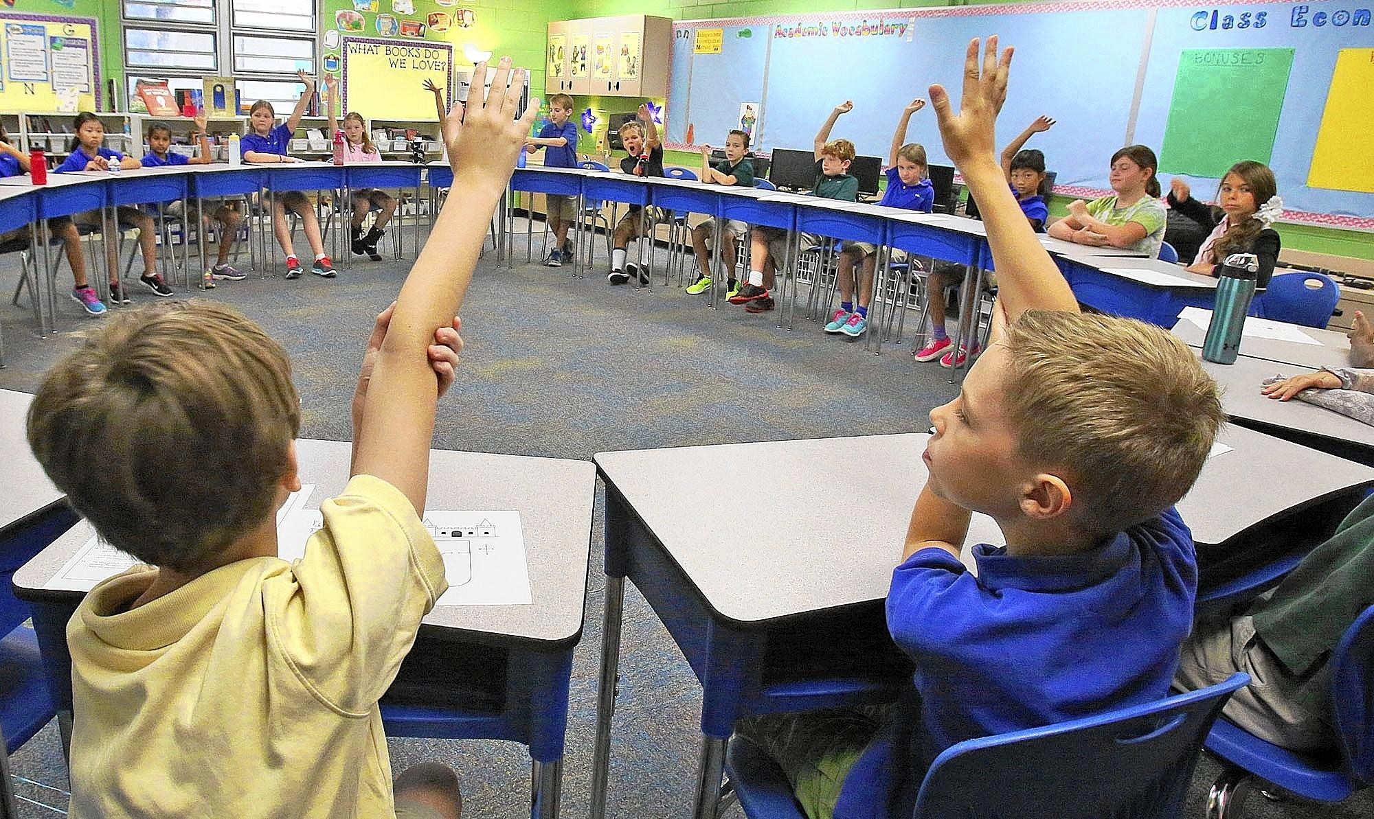 Students at Galileo School of Gifted Learning in Sanford raise their hands when asked a question by Language Arts teacher Jana Spitalnick