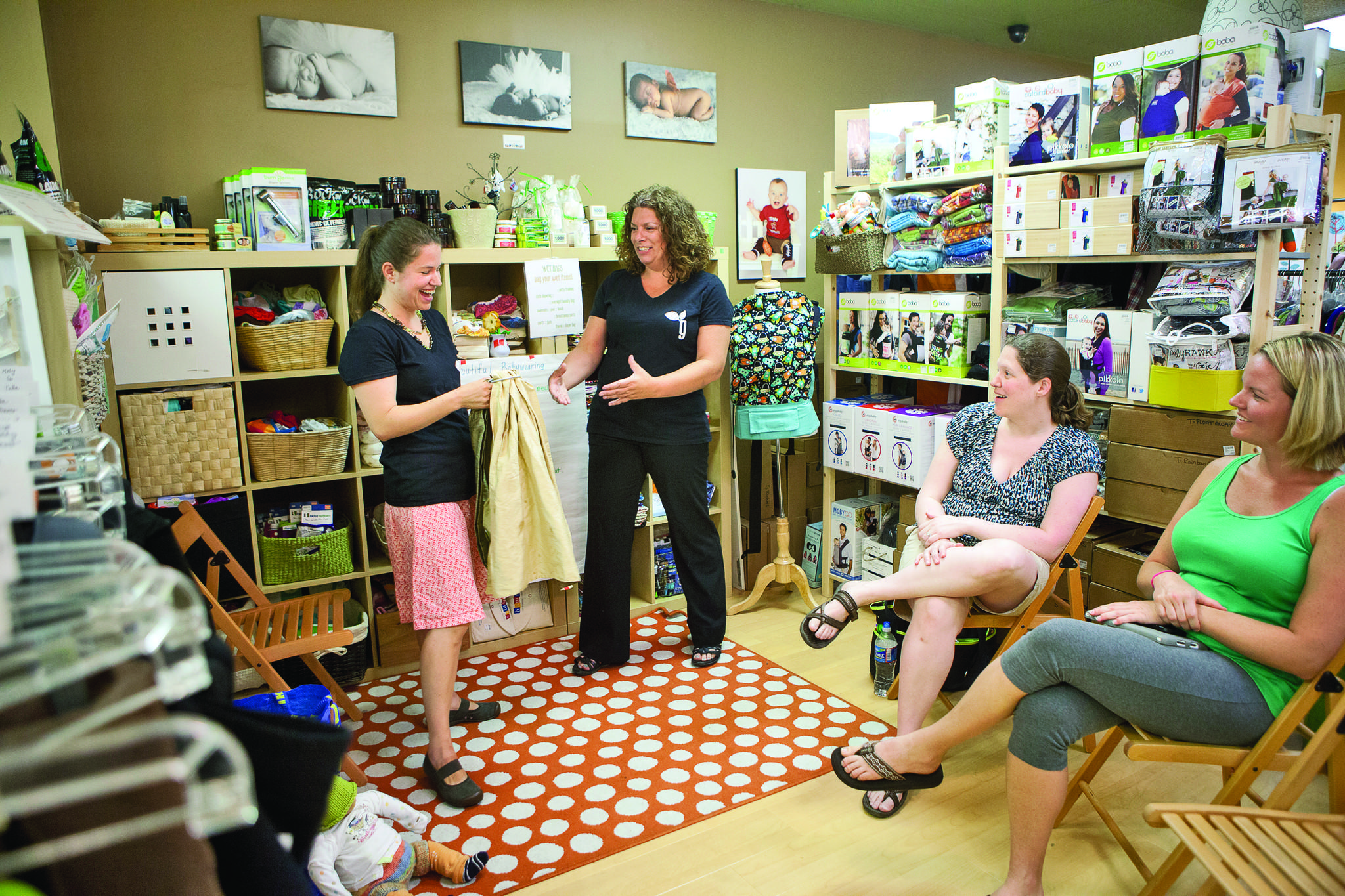 Center for Babywearing Studies Lead Educator Amy Takemoto, left, of Guilford and owner Rachel Baliff, center, talk about baby carriers during a baby wearing 101 class at Greenberries in Columbia, Md.