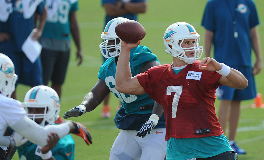 Miami Dolphins quarterback Brady Quinn throws a pass during training camp, Tuesday, Aug. 12, 2014, at Nova Southeastern University in Davie.