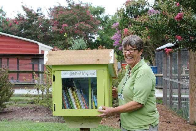 Rhonda Graves stands next to a Little Free Library built at Bluebird Gap Farm in Hampton.