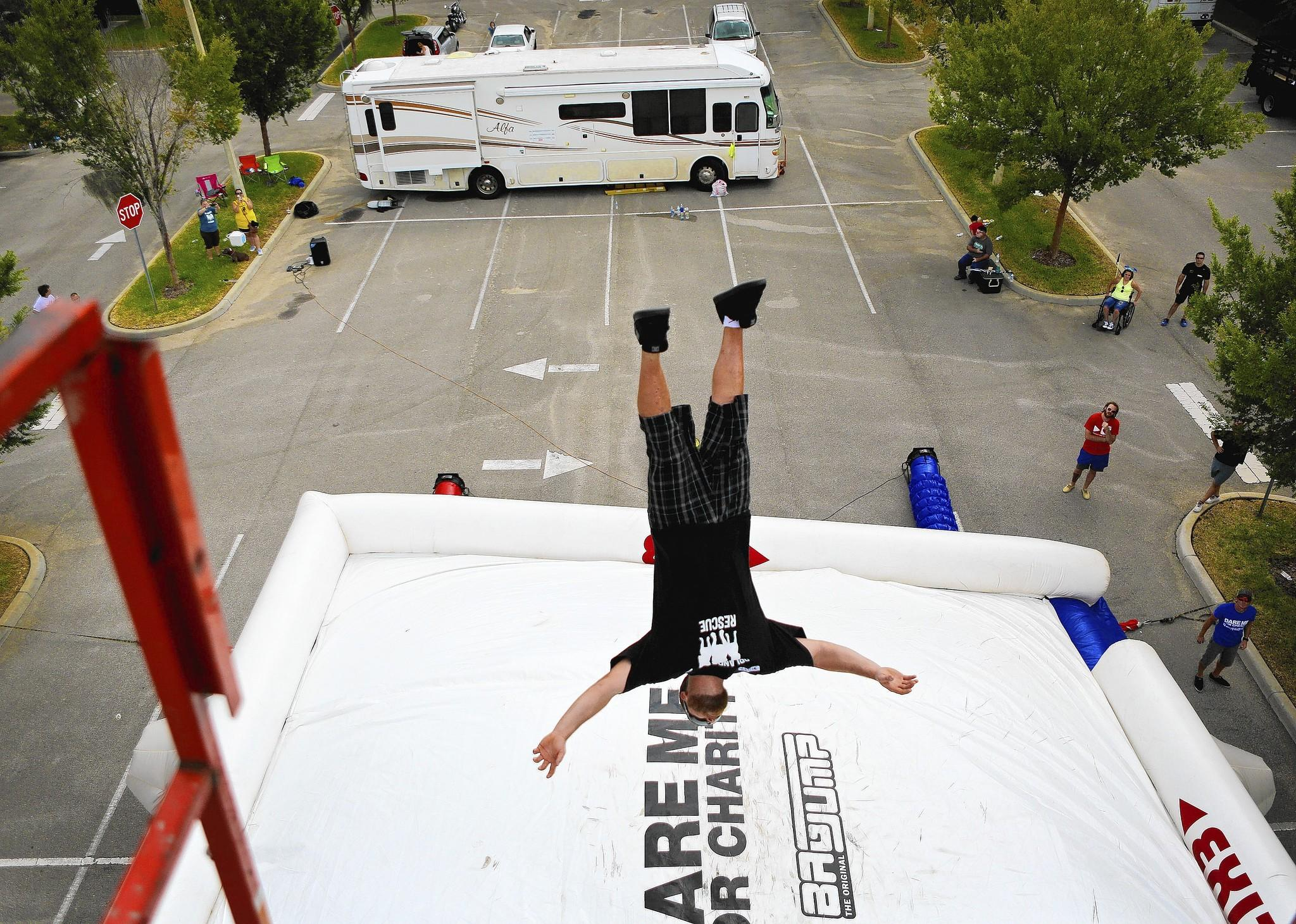 "Roy Tincher jumps from a platform onto a giant air bag to help raise money for the Orlando Bully Rescue on Tuesday, August 12, 2014. People from around Florida jumped for the chance to raise money for their favorite charity and to be part of a new tv show. The ""Dare Me for Charity"" pilot was being filmed in Sanford at Harvest Time International. (Jacob Langston/Orlando Sentinel) ORG XMIT: dare-me-for-charity-jumpers"