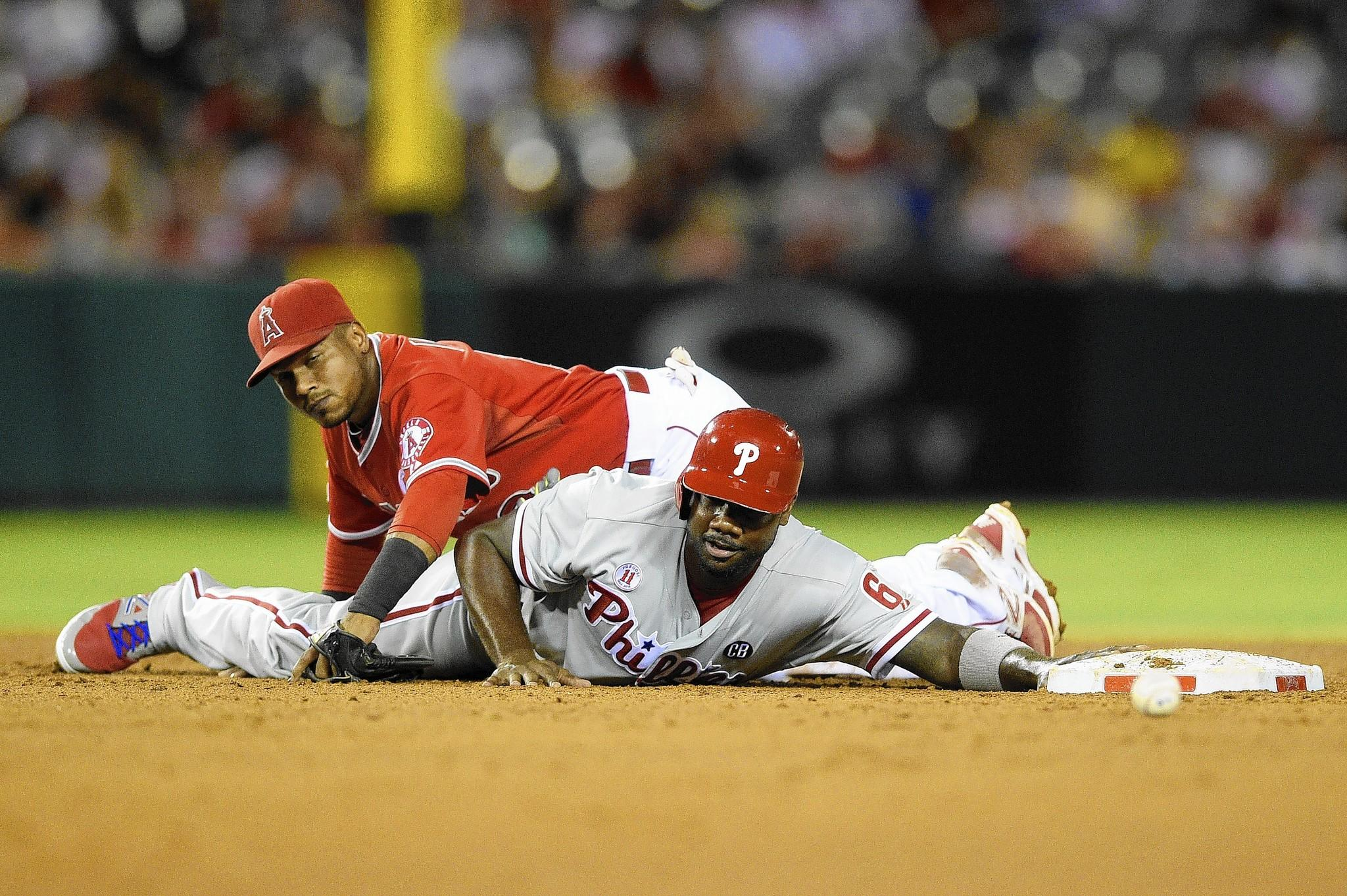 Los Angeles Angels shortstop Erick Aybar (top) is unable to catch an attempted pickoff throw as Philadelphia Phillies designated hitter Ryan Howard dives back to second base during the sixth inning at Angel Stadium of Anaheim.