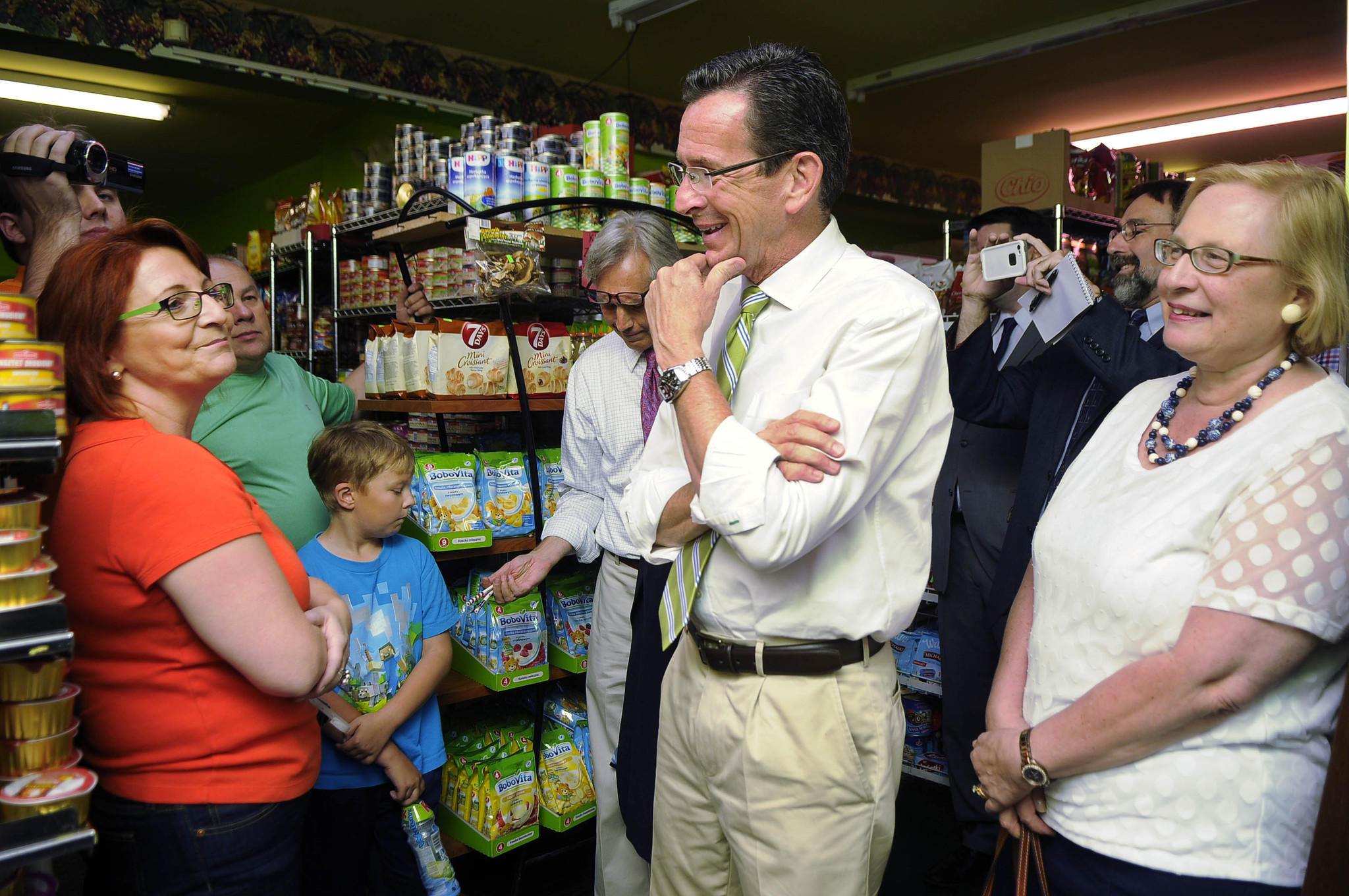 Gov. Dannel Malloy visits with Beata and Slawek Rulka (left) and their son, Jacob, 9, at Zieleniak Green Grocer Deli on Broad Street in New Britain Thursday evening as his re-election campaign gets underway. Malloy was accompanied by Rep. Peter Tercyak (center, background) and Sen. Terry Gerratana (right) as he toured Broad Street in the heart of the city's Polish neighborhood.