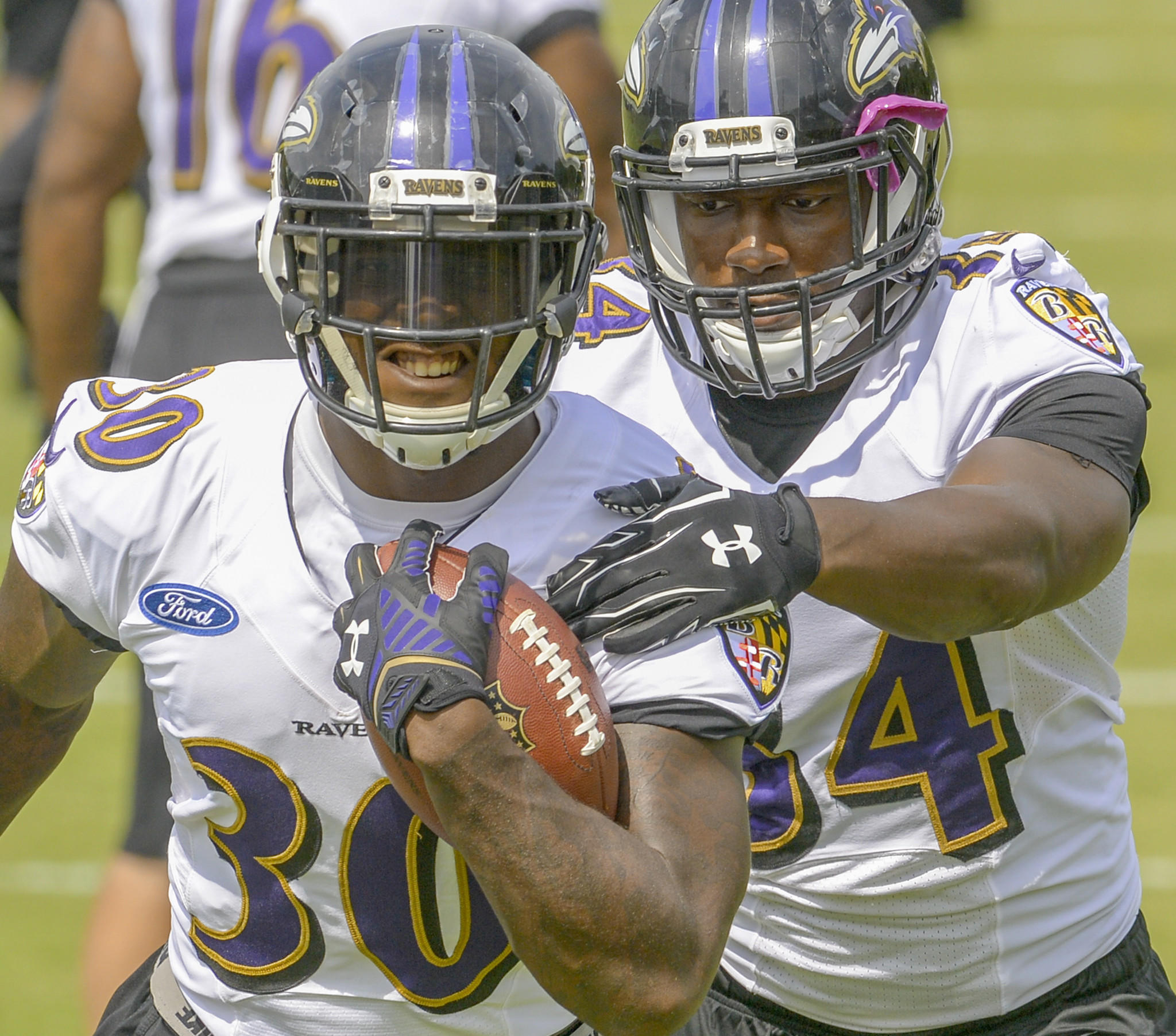 Ravens running backs Bernard Pierce and Lorenzo Taliaferro work against each other during a drill during training camp.