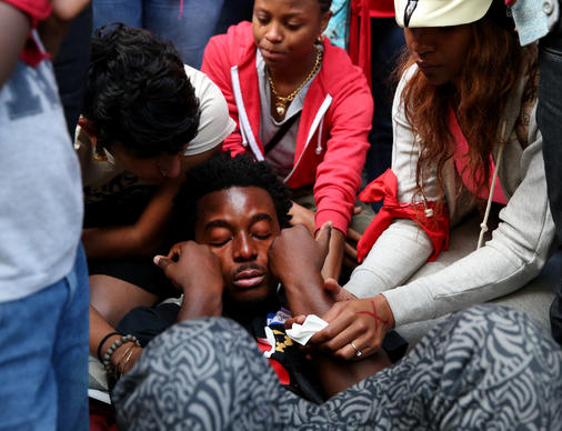 Protest organizer Malcolm London, 21, crumples to the ground after being overcome with emotion during a Thursday vigil at Daley Plaza to mark the shooting death of Michael Brown in Ferguson, Mo.