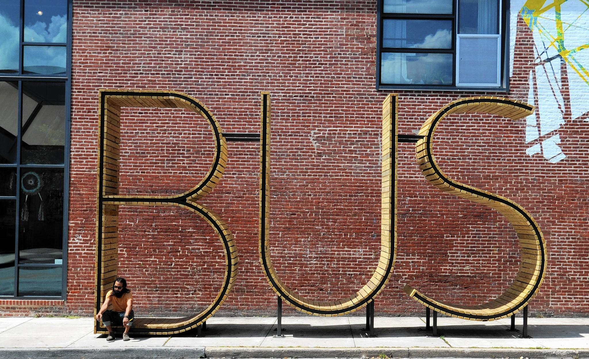 Artist Pablo Machioli takes a break in the B-U-S sculpture outside the Creative Alliance.