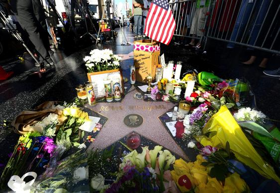 Flowers and tributes are placed at the make-shift memorial on the Hollywood Walk of Fame star for Robin Williams.