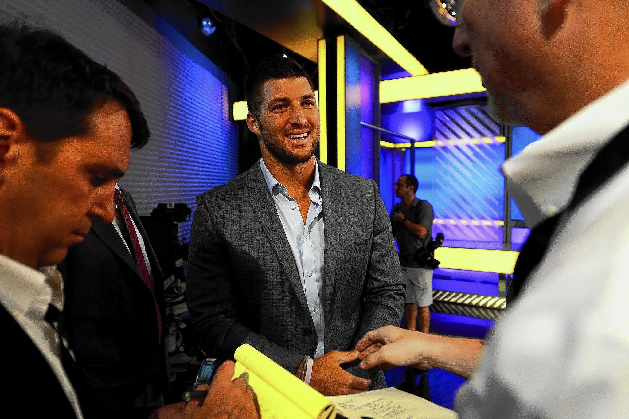 Analyst Tim Tebow, center, smiles as he answers questions from the media on the set of SEC Nation at the ESPN studios in Charlotte, N.C., on Wednesday, Aug. 6, 2014.