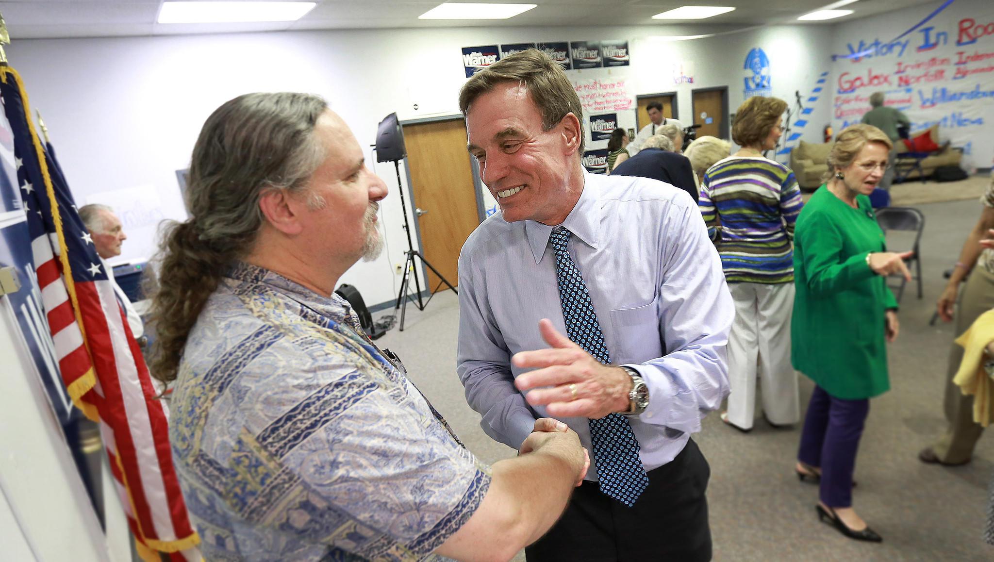 Virginia Senator Mark Warner, right, shakes the hand of Tim Dolan, who has come to meet the senator, who has just opened a campaign office in Hampton.