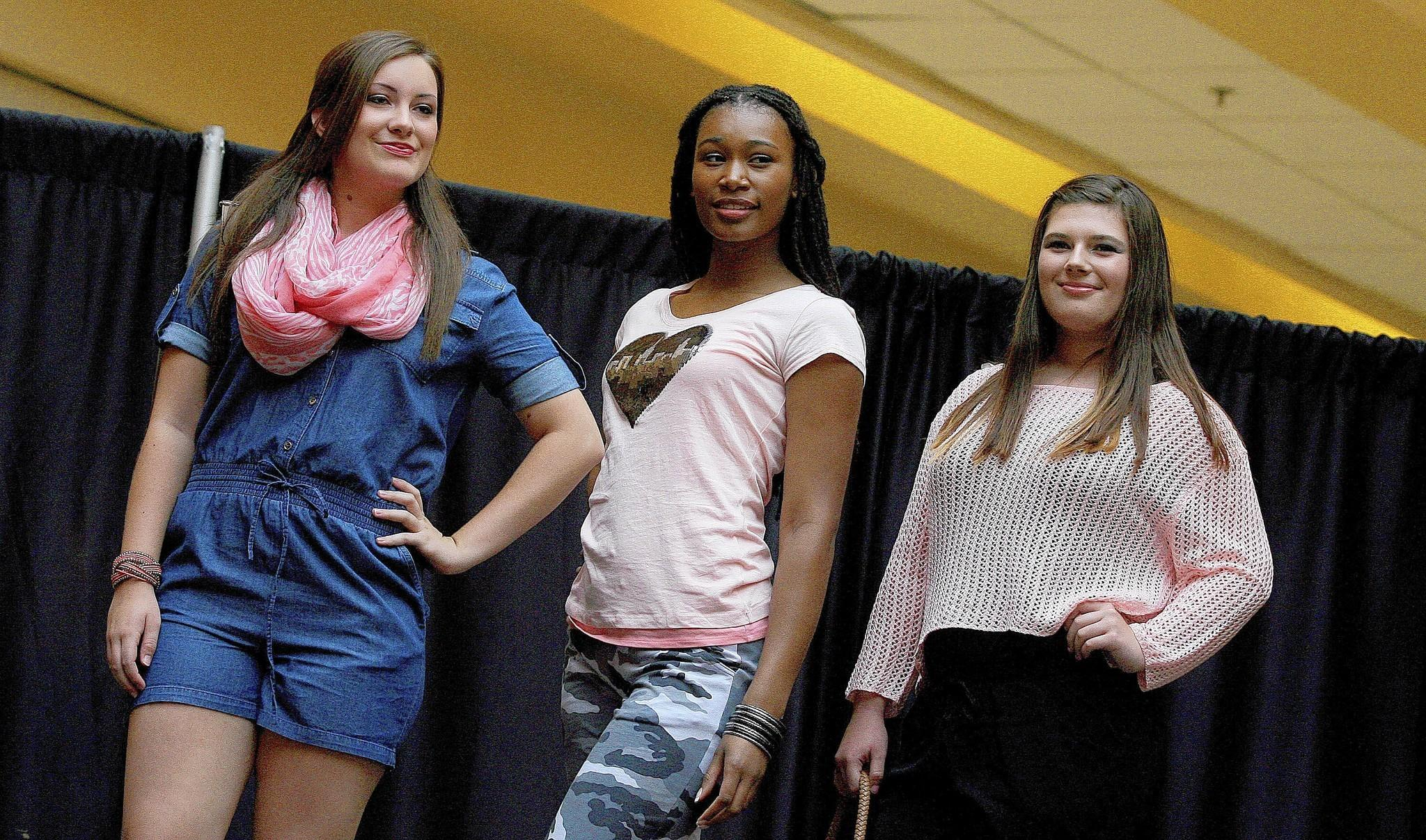 Sydney Cook, Tiarra Johnson and Jenna Davidson model the latest in back-to-school fashion Saturday at Patrick Henry Mall.