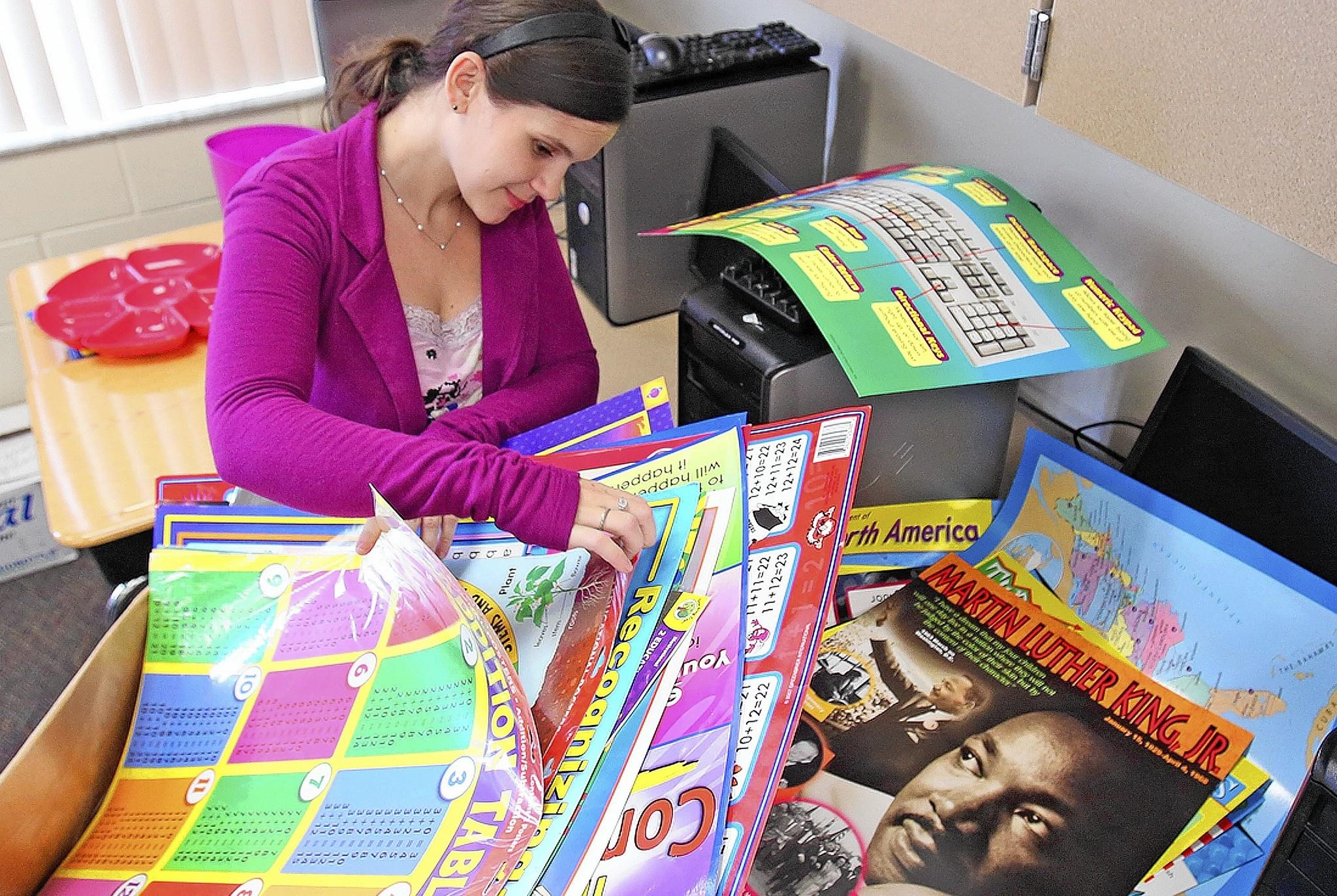 Stephanie Casternopoulos ,26, sorts through some of her posters Monday, August 4, 2014 to hang in her classroom. Casternopoulos recently graduated from UCF and is excited about starting her first job as a second-grade teacher at Minneola Charter Elementary.(Red Huber/ Staff Photographer)