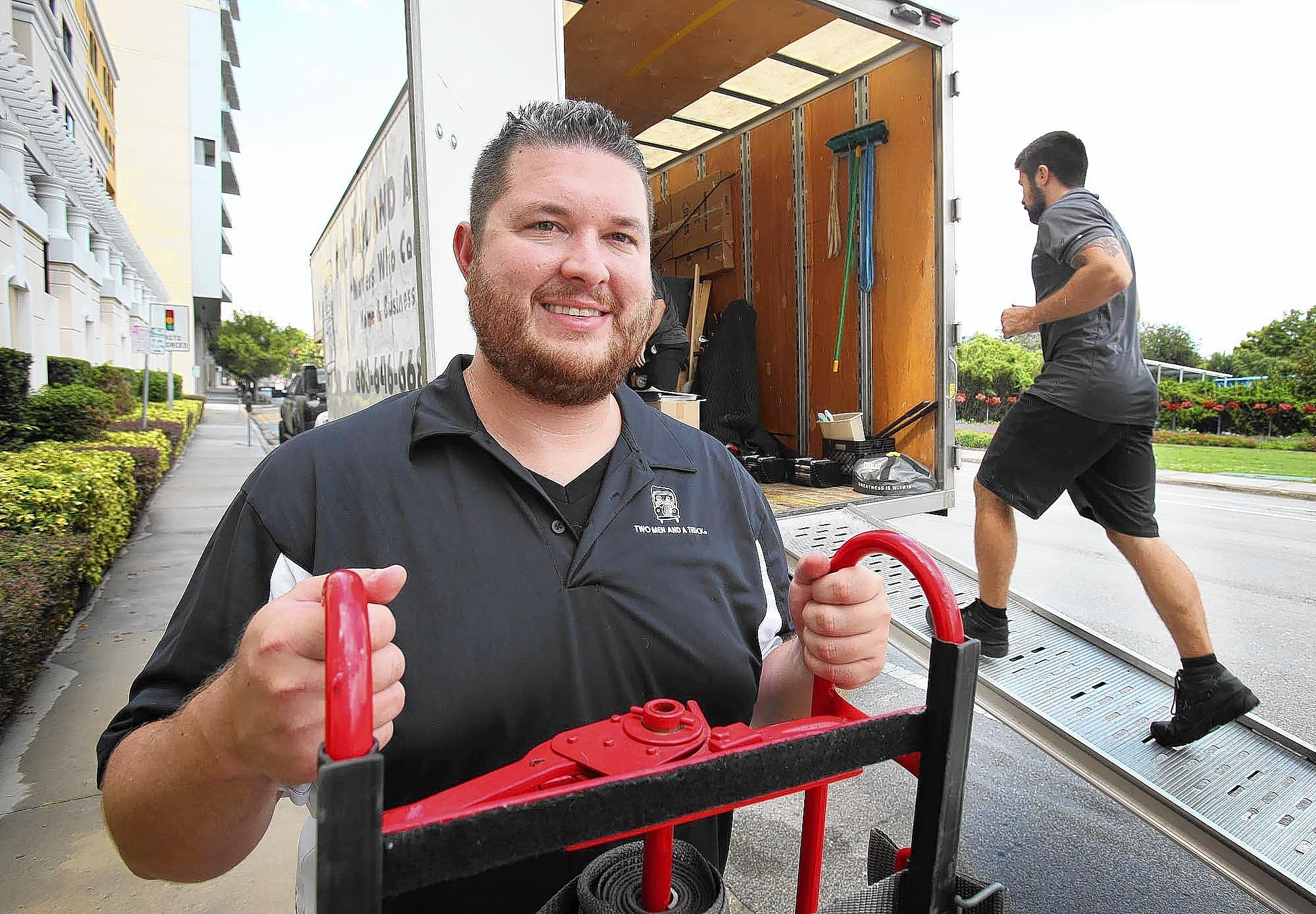 Jonathan Crain, owner of a Two Men and a Truck franchise, is pictured at one of his trucks as his 2-man crew moves items into an apartment building in downtown Orlando on Thursday, August 7, 2014.