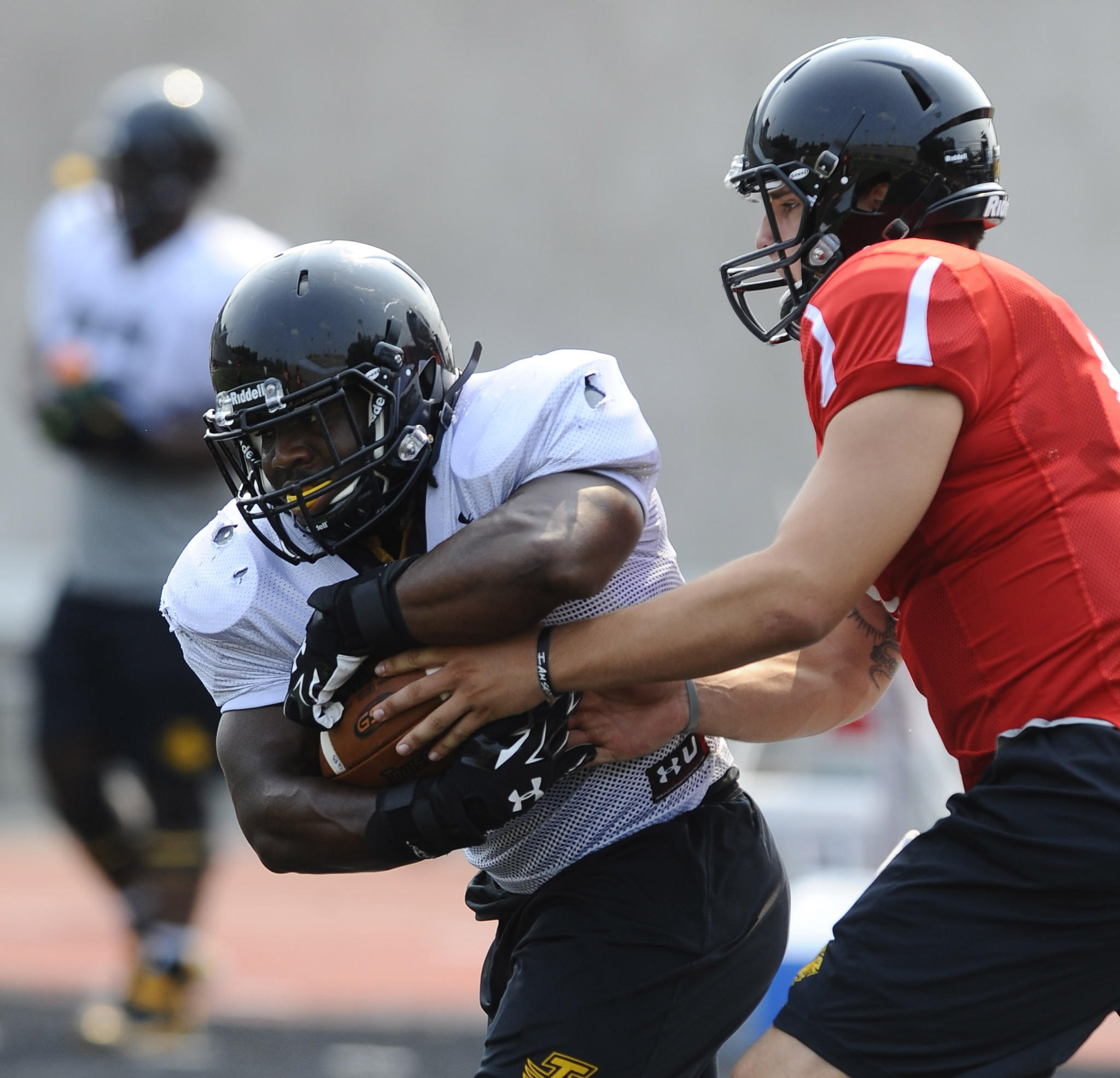 Towson football running back Darius Victor takes a handoff from quarterback Ellis Knudson during practice at Johnny Unitas Stadium.