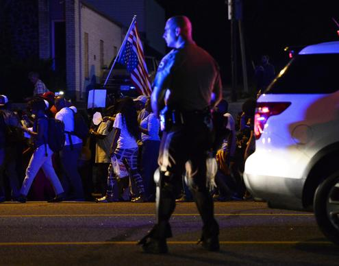 Police officers stand along a street on Monday as demonstrators protest the shooting death of Michael Brown in Ferguson, Mo.